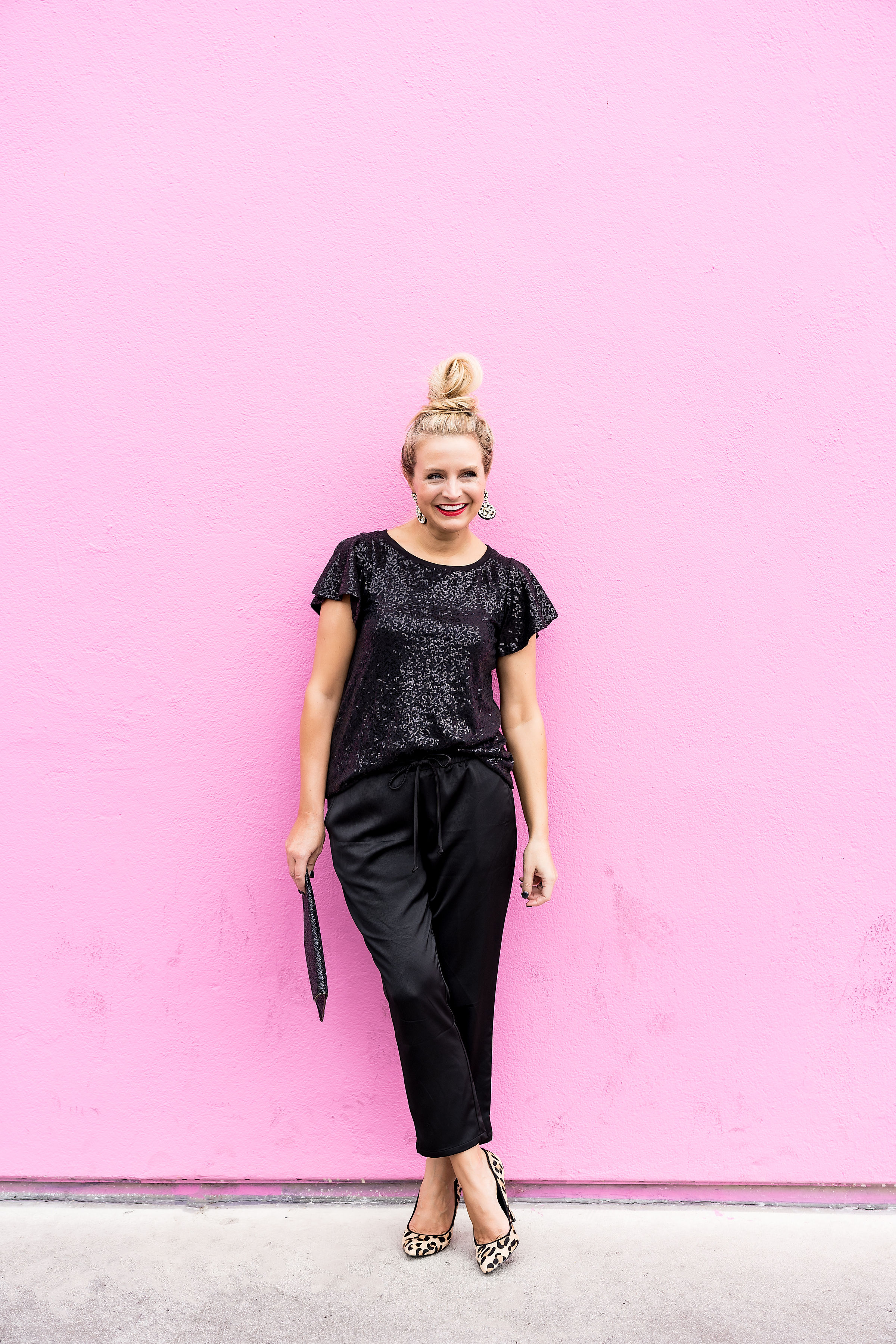 Top Houston fashion blogger, Fancy Ashley, features 7 Holiday Outfits perfect for the season: image of a woman wearing Black sequin tee, black jogger pants, Kate Spade earrings, glitter clutch and sam Edelman leopard pumps all available at Nordstrom