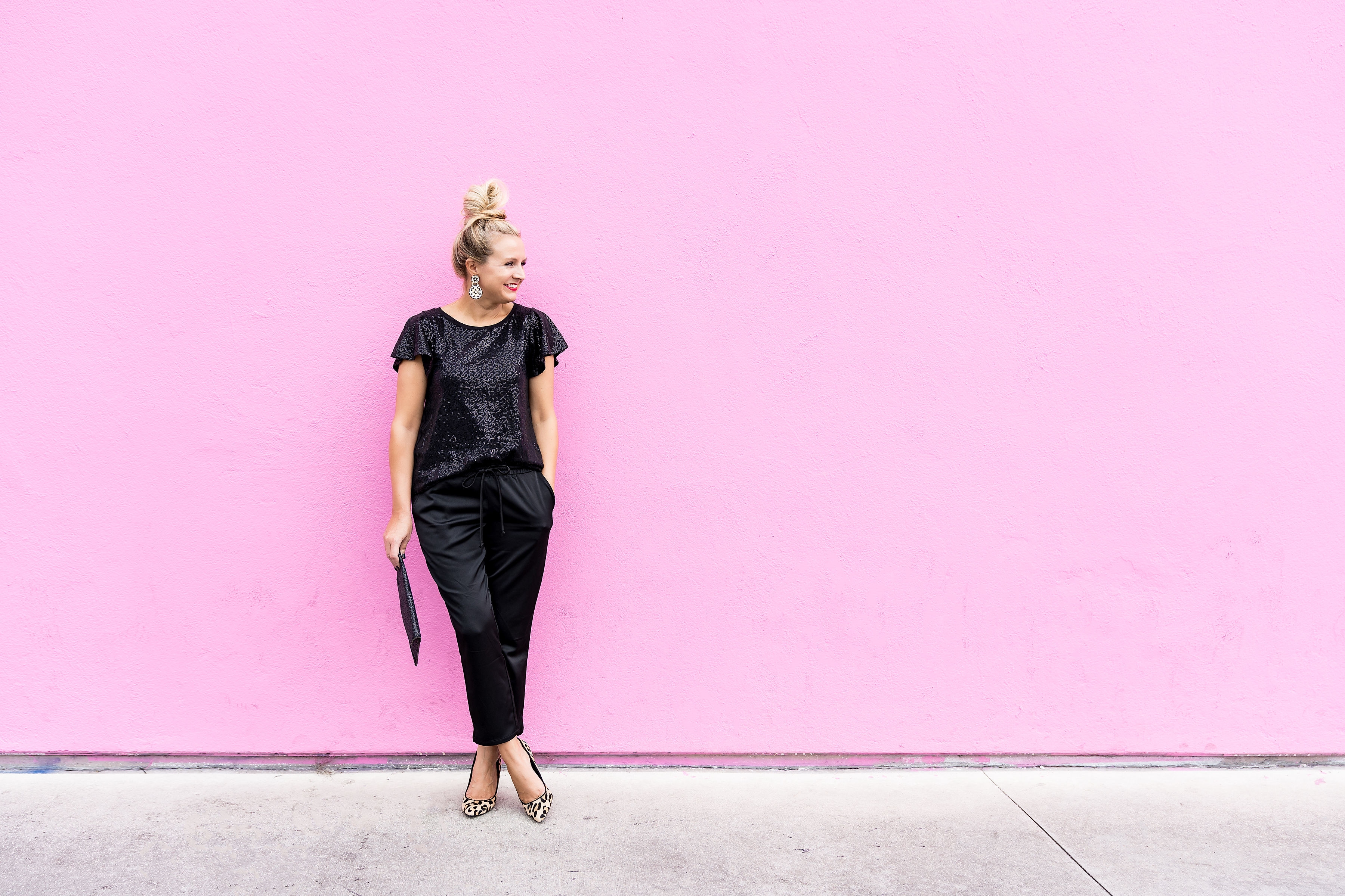 Gibson x Glam Collection Outfits featured by top Houston fashion blog, Fancy Ashley: a blonde woman stood against a wall wearing gibson x glam black sequin tops and silk joggers