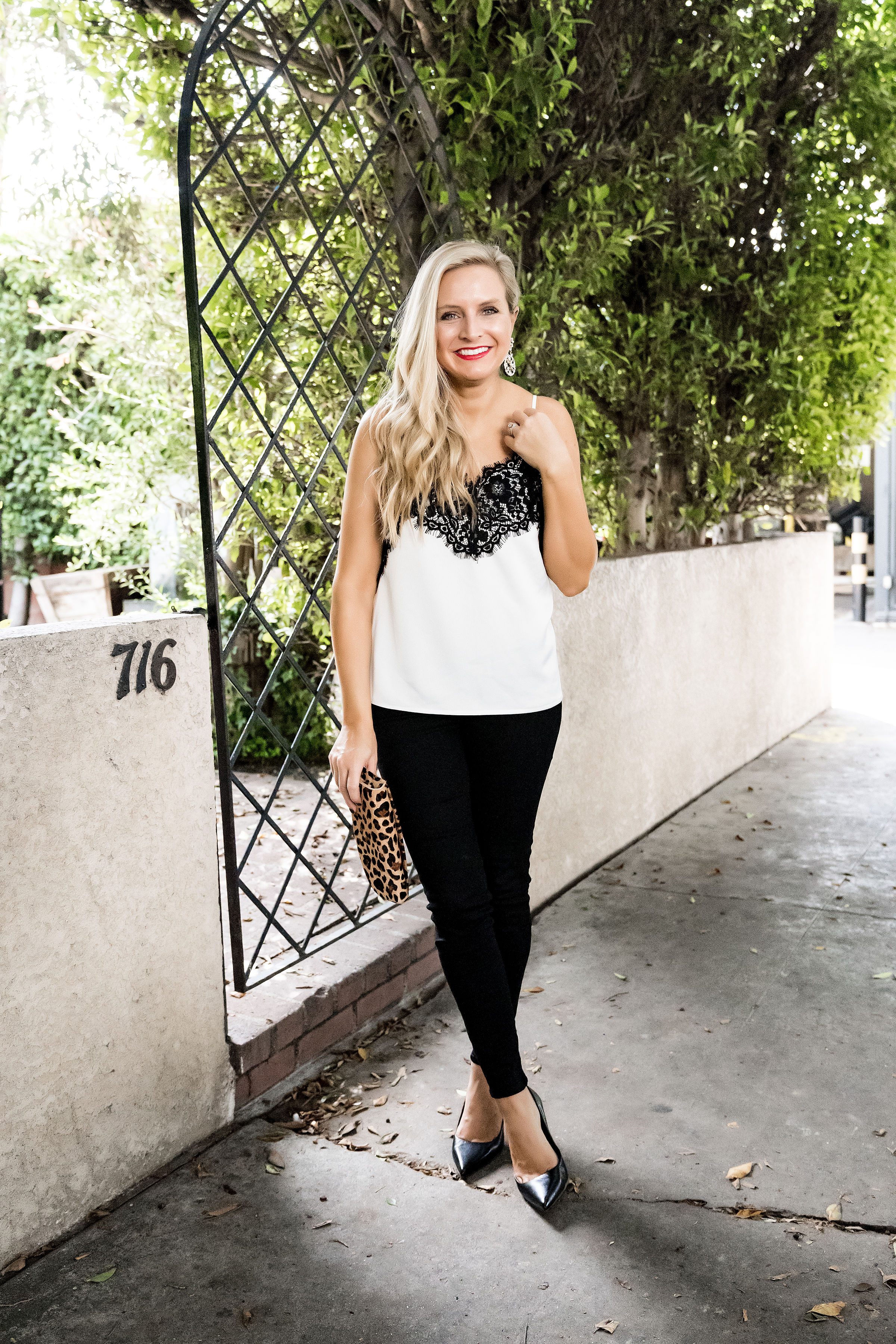 Gibson x Glam Collection Outfits featured by top Houston fashion blog, Fancy Ashley: a blonde woman walking wearing lace camisole, black denim jeans, black heels, leopard clutch