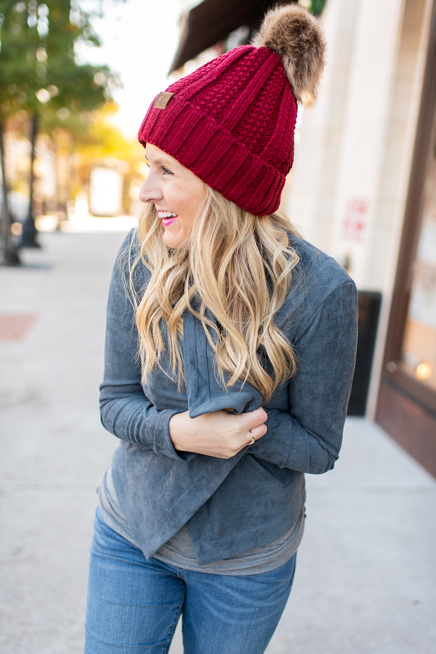 Fancy Ashley x Social Threads collection featured by top Houston fashion blogger, Fancy Ashley: image of a woman wearing a Social Threads faux suede jacket, Social Threads festive graphic tee, Social Threads skinny jeans, Social Threads Pom Paom Hat and Golden Goose sneakers