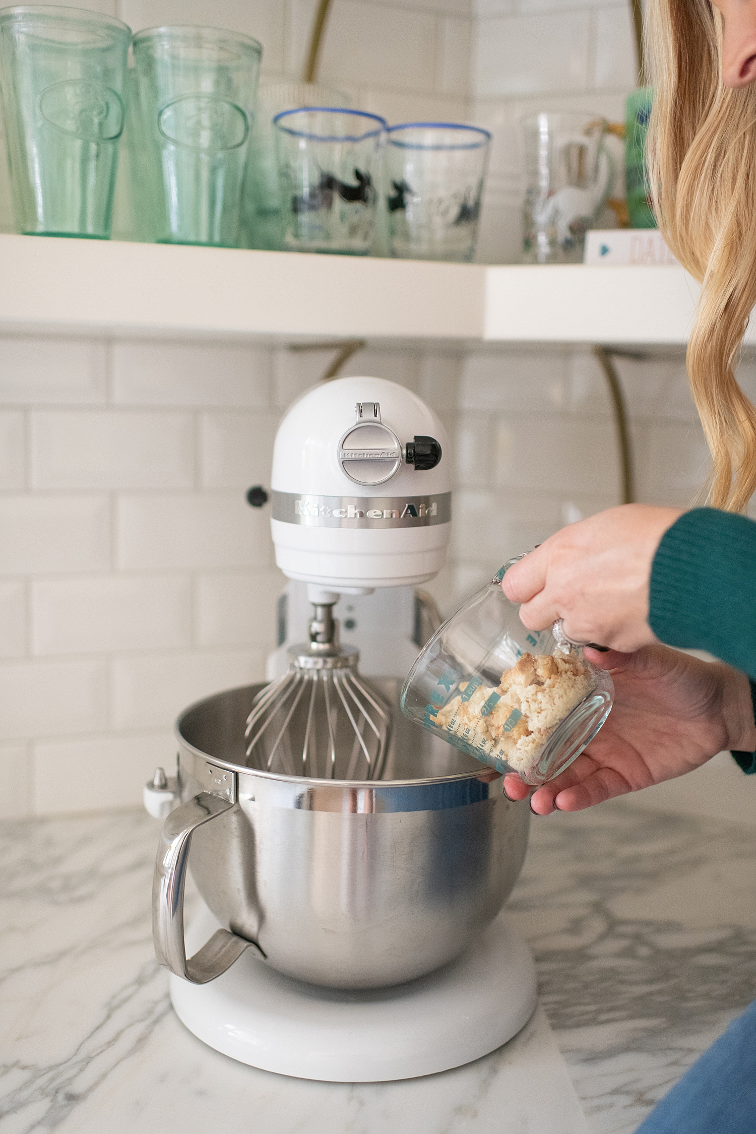 Gluten Free Sugar Cookie Truffles featured by top Houston lifestyle blog, Fancy Ashley: blonde woman sat on countertop pouring ingredients for her sugar cookie truffles