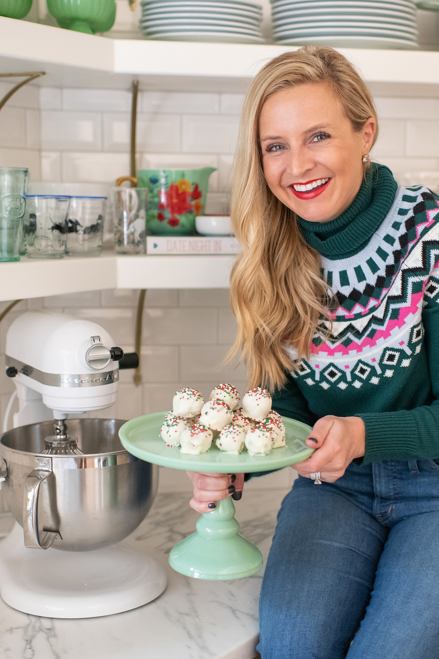 Gluten Free Sugar Cookie Truffles featured by top Houston lifestyle blog, Fancy Ashley: blonde woman sat on countertop holding a plate of gluten free sugar cookie truffles