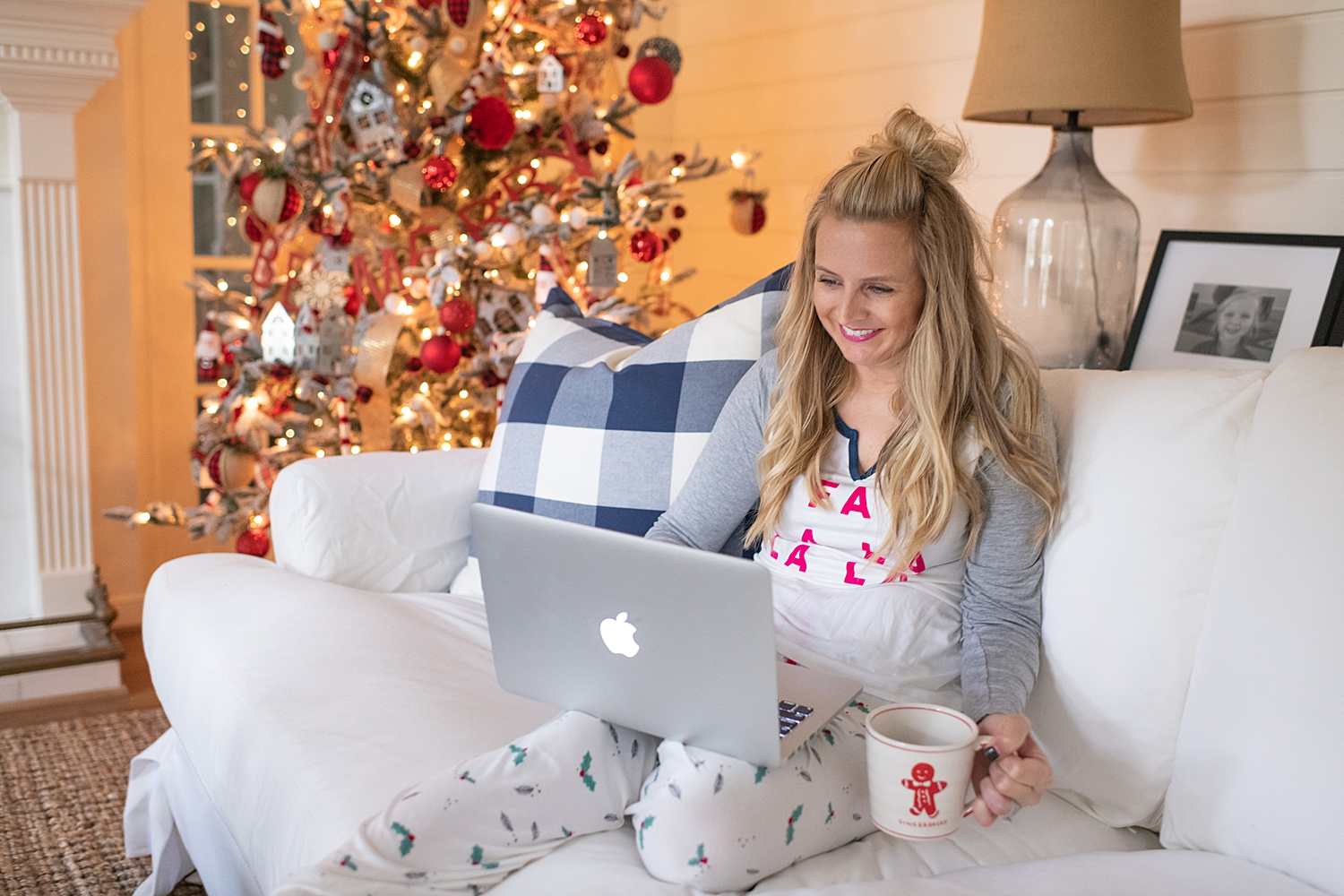 The Ultimate Cyber Monday Shopping Deals featured by top Houston life and style blogger, Fancy Ashley: picture of a blonde woman wearing Holidays PJs, sat on an armchair and looking at her Apple laptop
