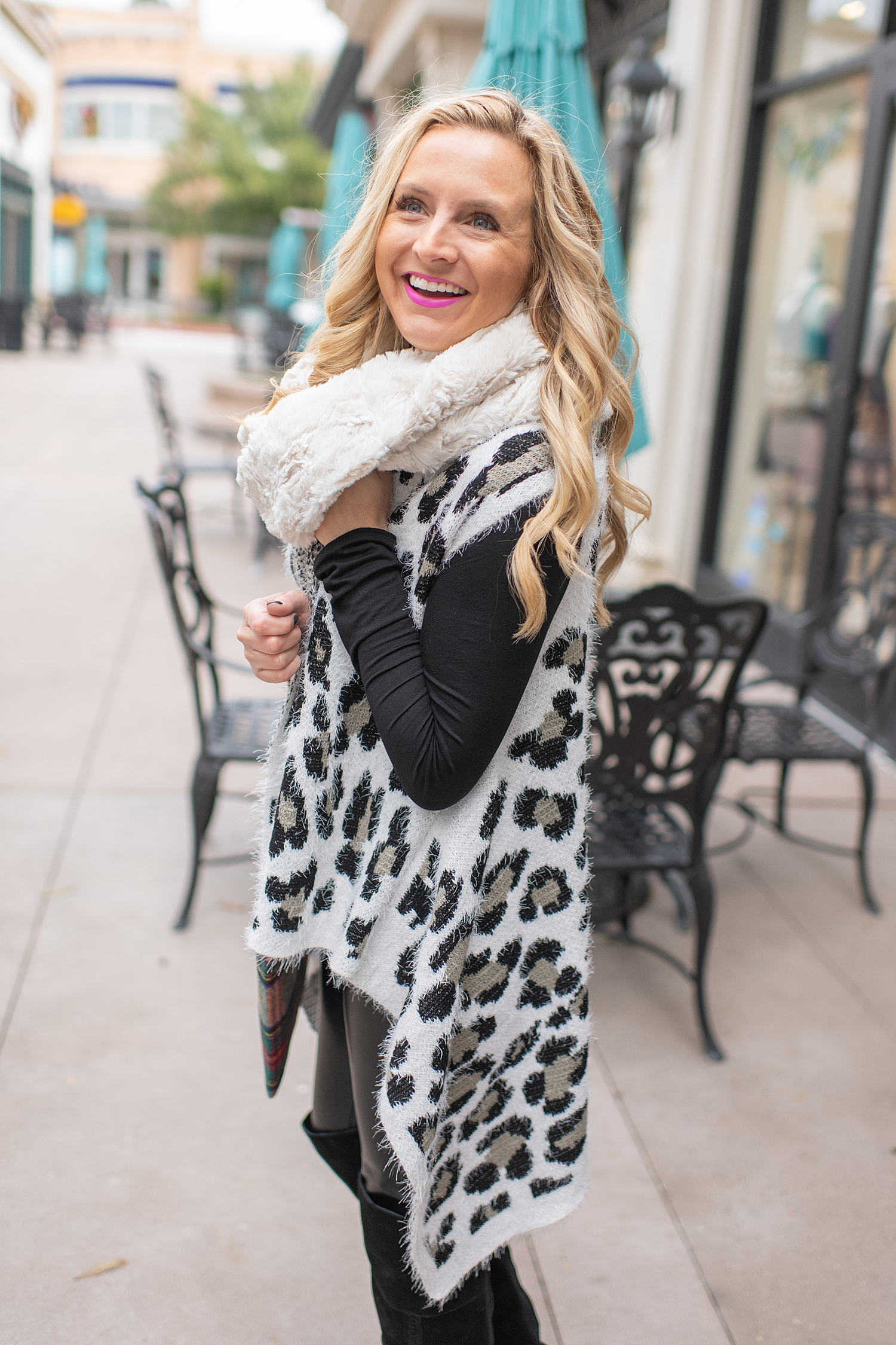 Fancy Ashley x Social Threads collection featured by top Houston fashion blogger, Fancy Ashley: image of a woman wearing a Social Threads Leopard vest, Social Threads faux leather leggings, Social Threads plaid clutch, Social Threads white infinity scarf and Vince Camuto Over the Knees Boots