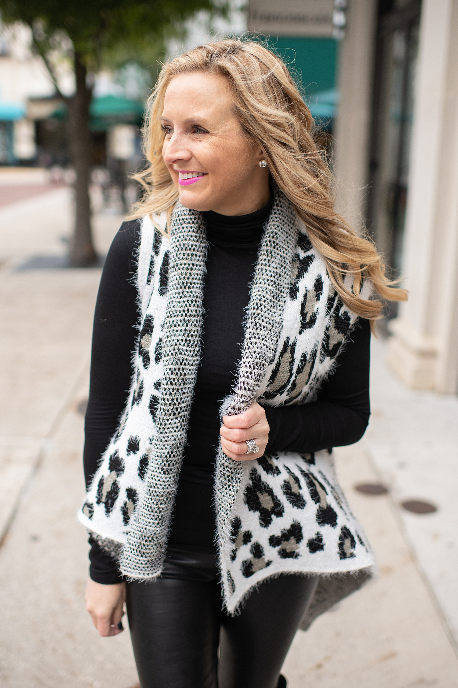 Fancy Ashley x Social Threads collection featured by top Houston fashion blogger, Fancy Ashley: image of a woman wearing a Social Threads Leopard vest, Social Threads faux leather leggings, Social Threads plaid clutch and Vince Camuto Over the Knees Boots