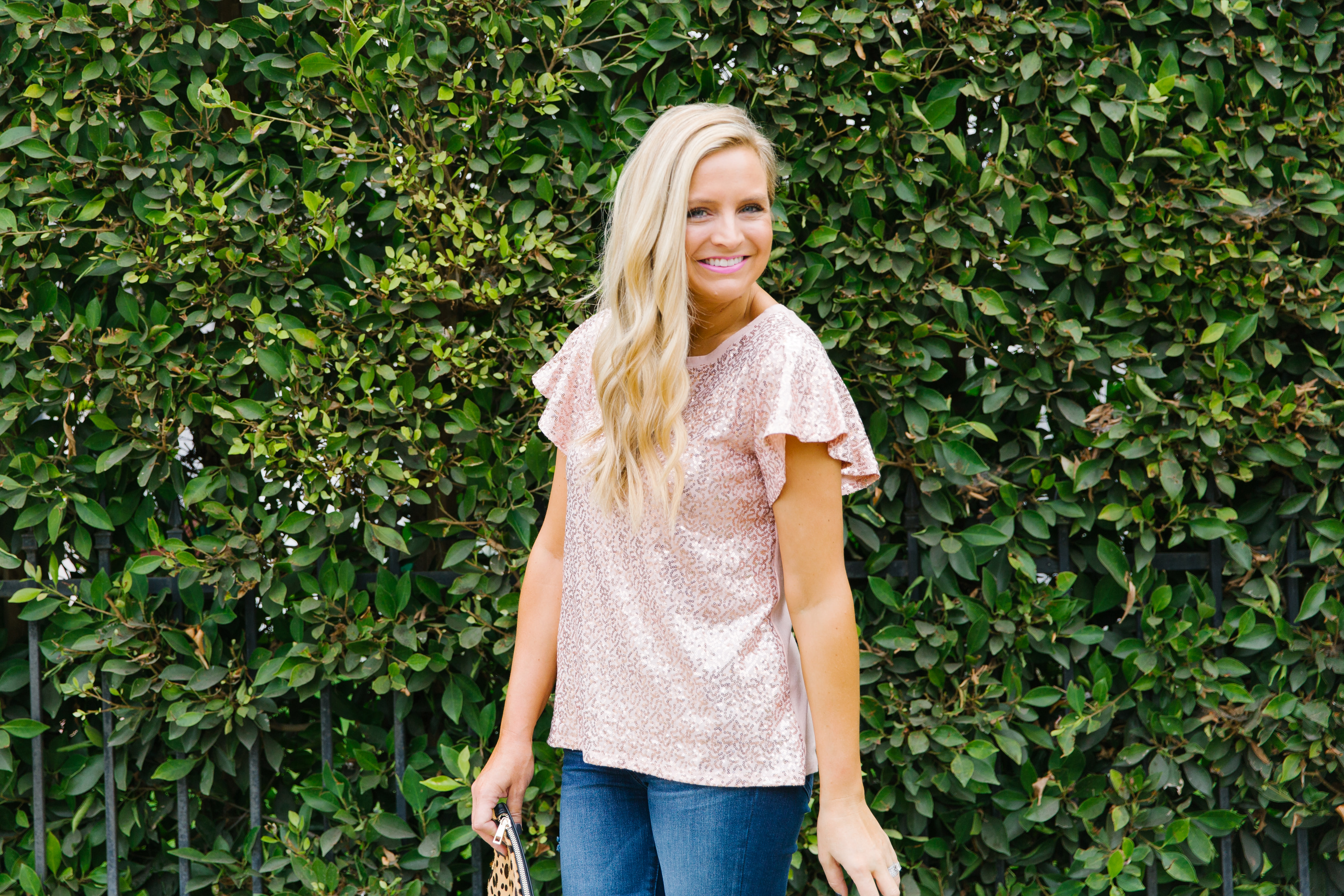 Gibson x Glam Collection Outfits featured by top Houston fashion blog, Fancy Ashley: a blonde woman walking wearing sequin flutter sleeves top, jeans, leopard clutch and pink heels