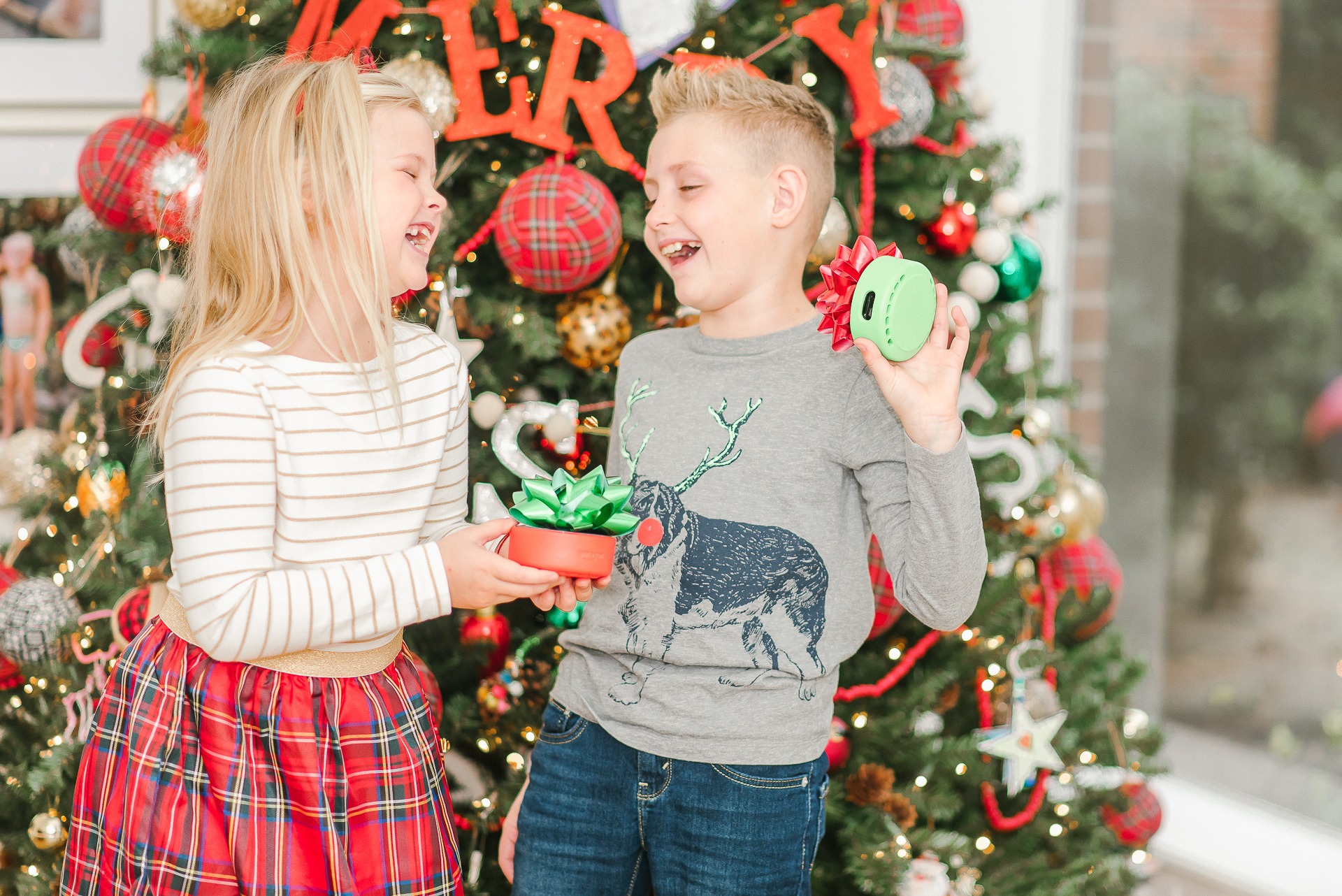 Echo Dot Kids Edition review featured by top Houston lifestyle blogger, Fancy Ashley: image of siblings holding wrapped Amazon Echos Kids Edition