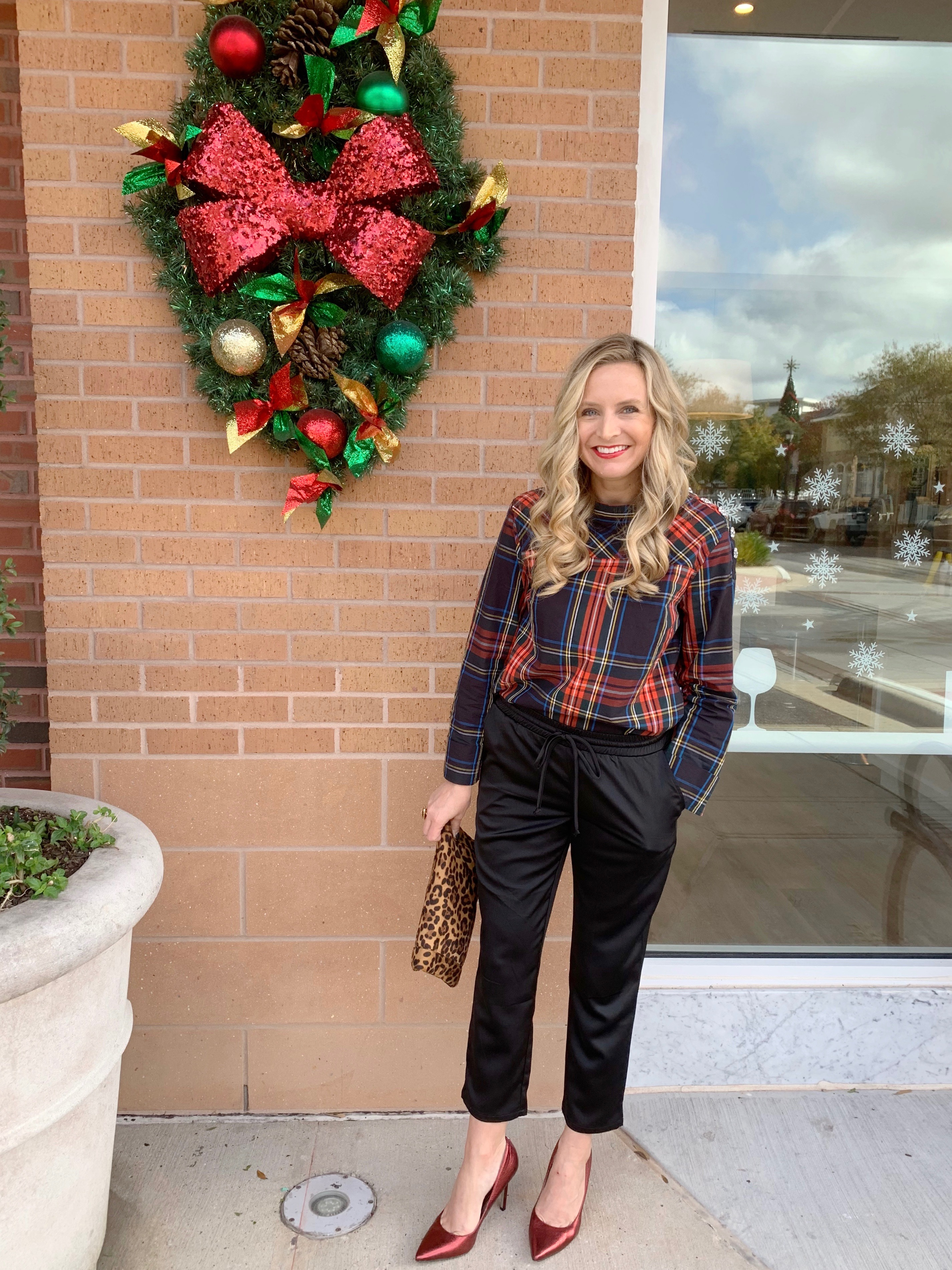 Top Houston fashion blogger, Fancy Ashley, features 7 Holiday Outfits perfect for the season: image of a woman wearing J.Crew plaid shirt, black jogger pants, Kate Spade earrings, leopard clutch and sam Edelman leopard pumps all available at Nordstrom