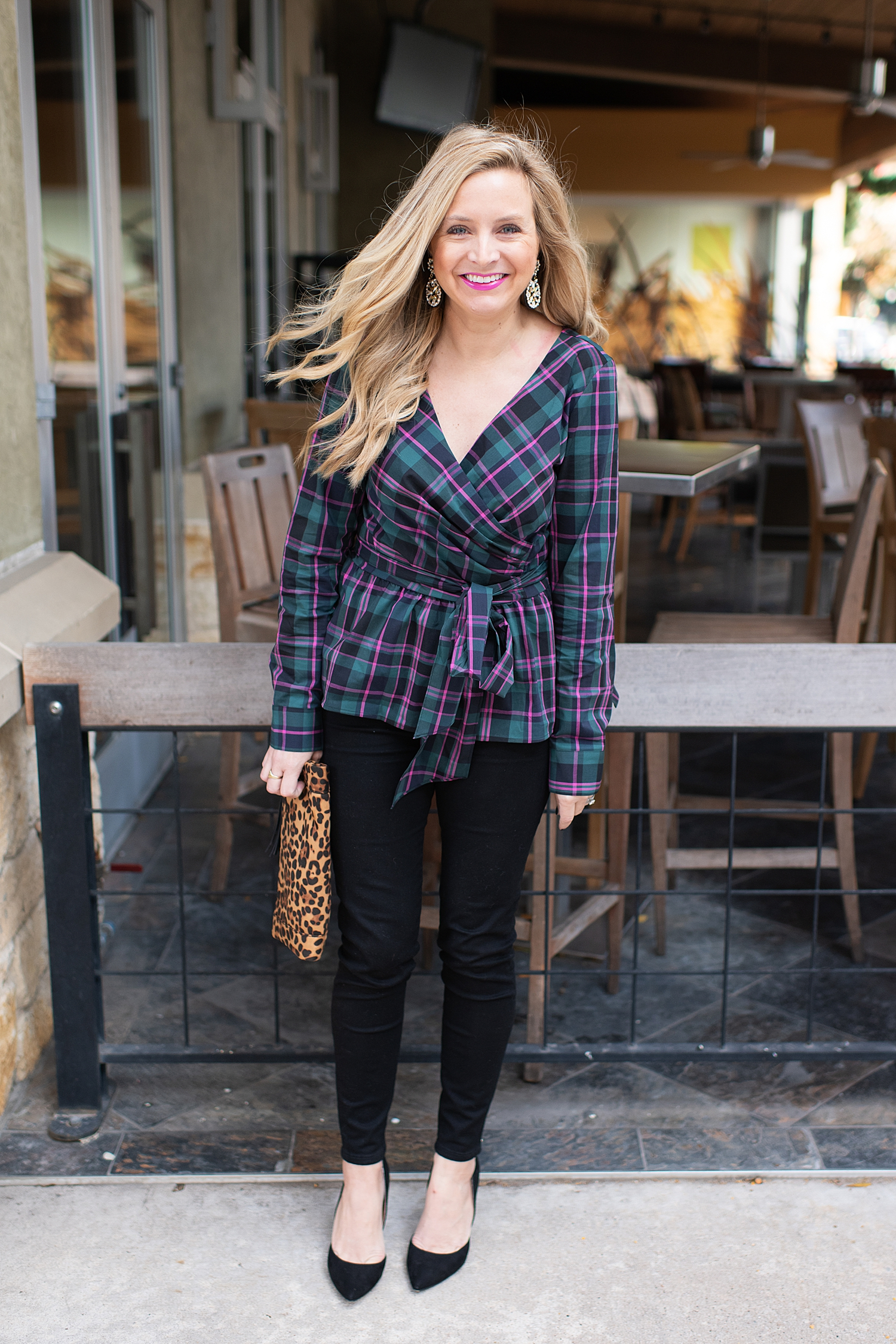 Top Houston fashion blogger, Fancy Ashley, features 7 Holiday Outfits perfect for the season: image of a woman wearing Plaid wrap top, black ankle skinny jeans, Kate Spade earrings, leopard clutch all available at Nordstrom