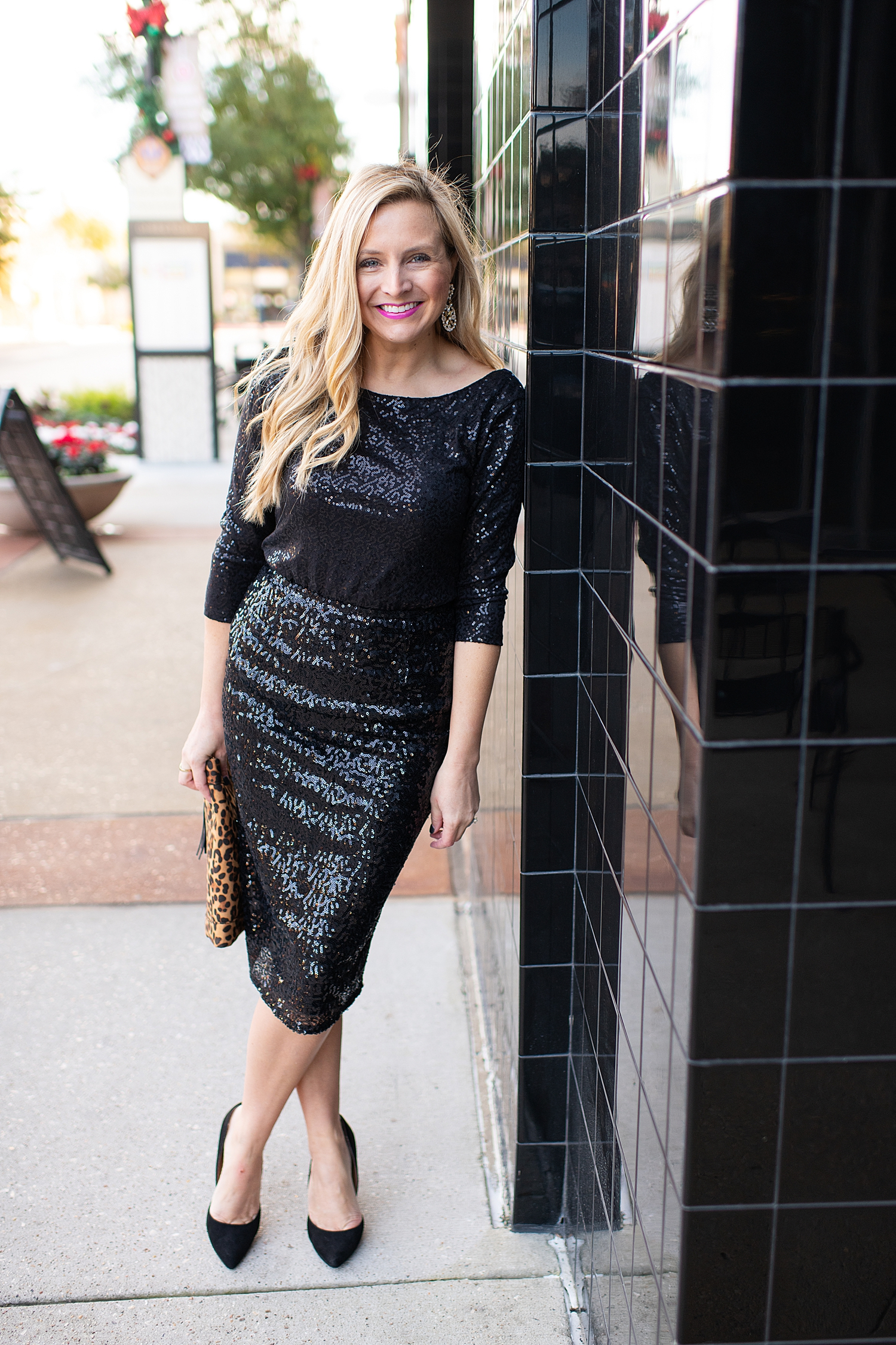 Top Houston fashion blogger, Fancy Ashley, features 7 Holiday Outfits perfect for the season: image of a woman wearing Black sequin top, sequin pencil skirt, Kate Spade earrings, leopard clutch all available at Nordstrom