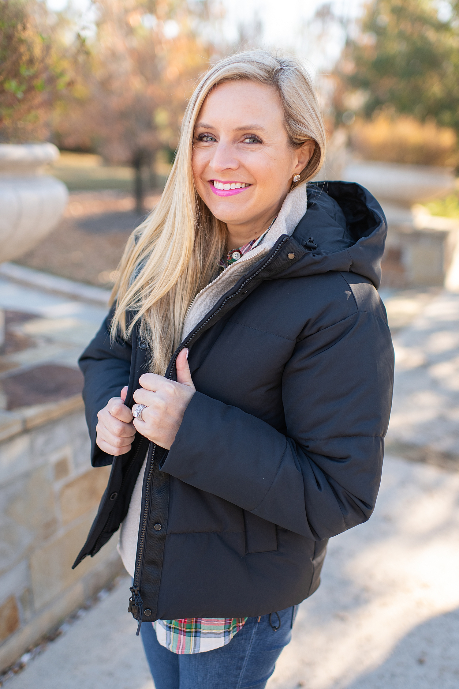The Best Cozy Gift Ideas featured by top Houston fashion blogger, Fancy Ashley: picture of a blonde woman wearing a black Everyone puffer jacket, Everlane zip fleece, J.Crew tartan shirt, J.Crew skinny jeans and Golden Goose sneakers