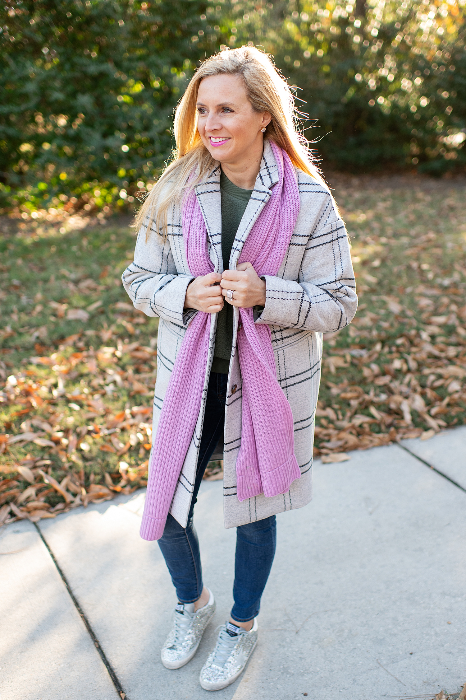 The Best Cozy Gift Ideas featured by top Houston fashion blogger, Fancy Ashley: picture of a blonde woman wearing an Everlane green cocoon coat, an Everlane cashmere scarf, an Everyone cashmere beanie, green Everlane fleece sweatshirt, J.Crew tartan shirt, J.Crew skinny jeans and Golden Goose sneakers