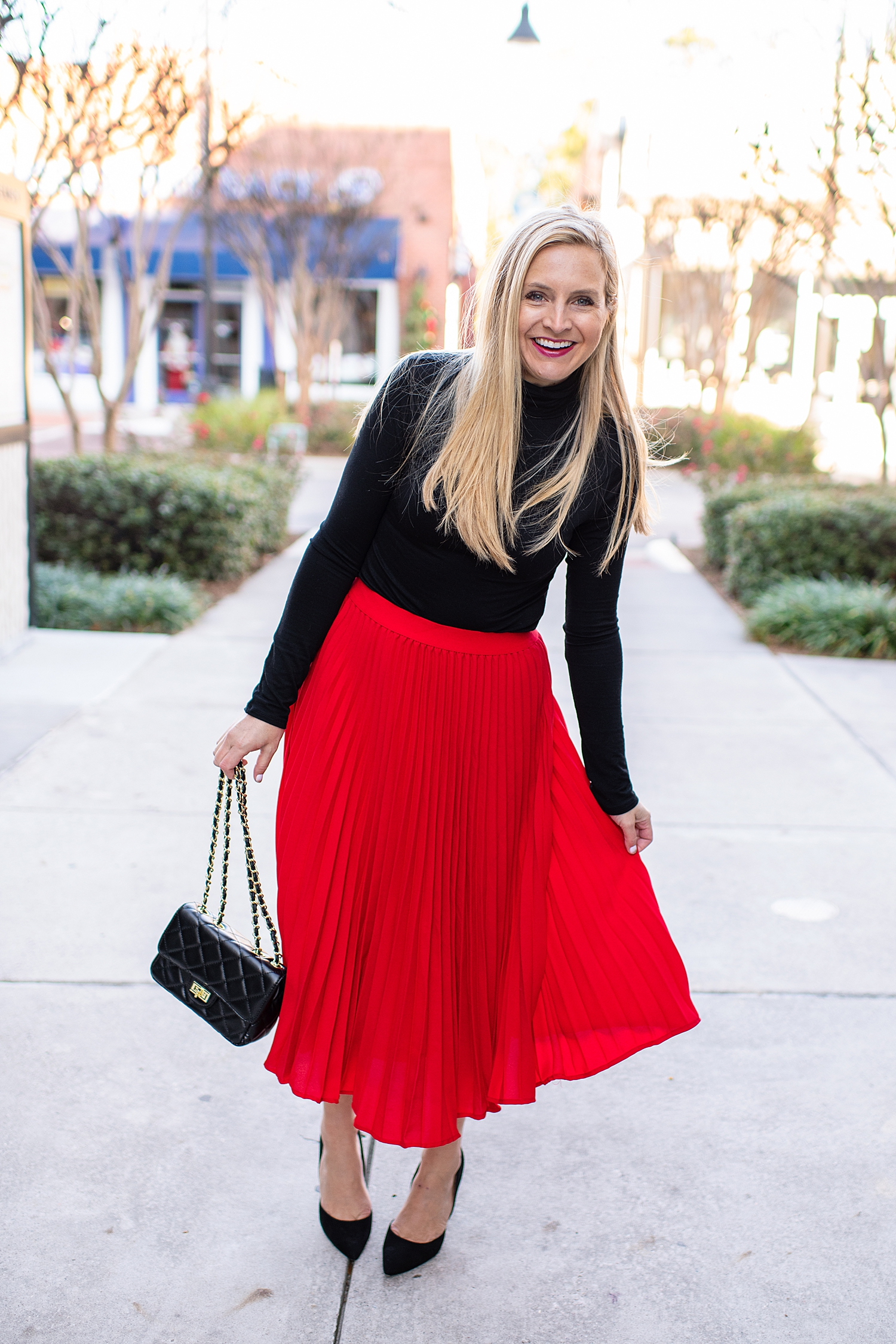 Winter fashion Amazon Favorites featured by top Houston fashion blogger, Fancy Ashley: image of a woman wearing a J.Crew black turtleneck, red high waist pleated skirt, black heels pumps and a quilted leather shoulder bag