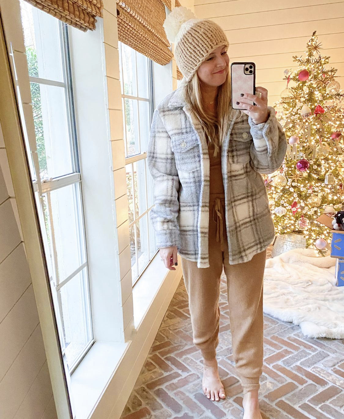 December Outfits by popular Houston fashion blog, Fancy Ashley: image of a woman standing in front of a Christmas tree decorated with pink, white and silver ornaments and wearing a tan and white pom beaning, tan sweater set, and grey and white plaid fleece jacket.