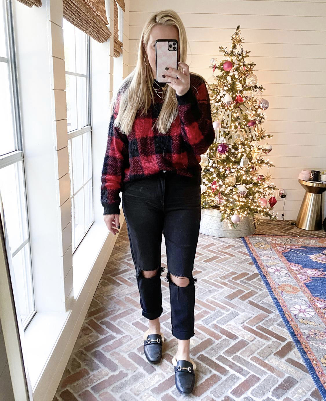 December Outfits by popular Houston fashion blog, Fancy Ashley: image of a woman standing in front of a Christmas tree decorated with pink, white and silver ornaments and wearing a red and black buffalo plaid shirt, black distressed jeans, and a black faux fur lined slide mules.
