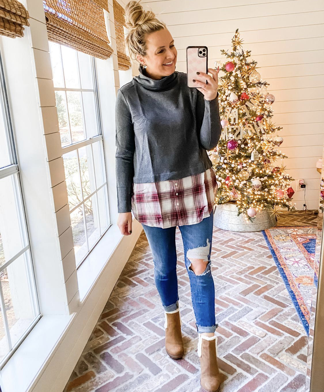 December Outfits by popular Houston fashion blog, Fancy Ashley: image of a woman standing in front of a Christmas tree decorated with pink, white and silver ornaments and wearing a grey and red and white plaid turtleneck shirt, distressed denim, and fur lined brown sueded ankle boots.