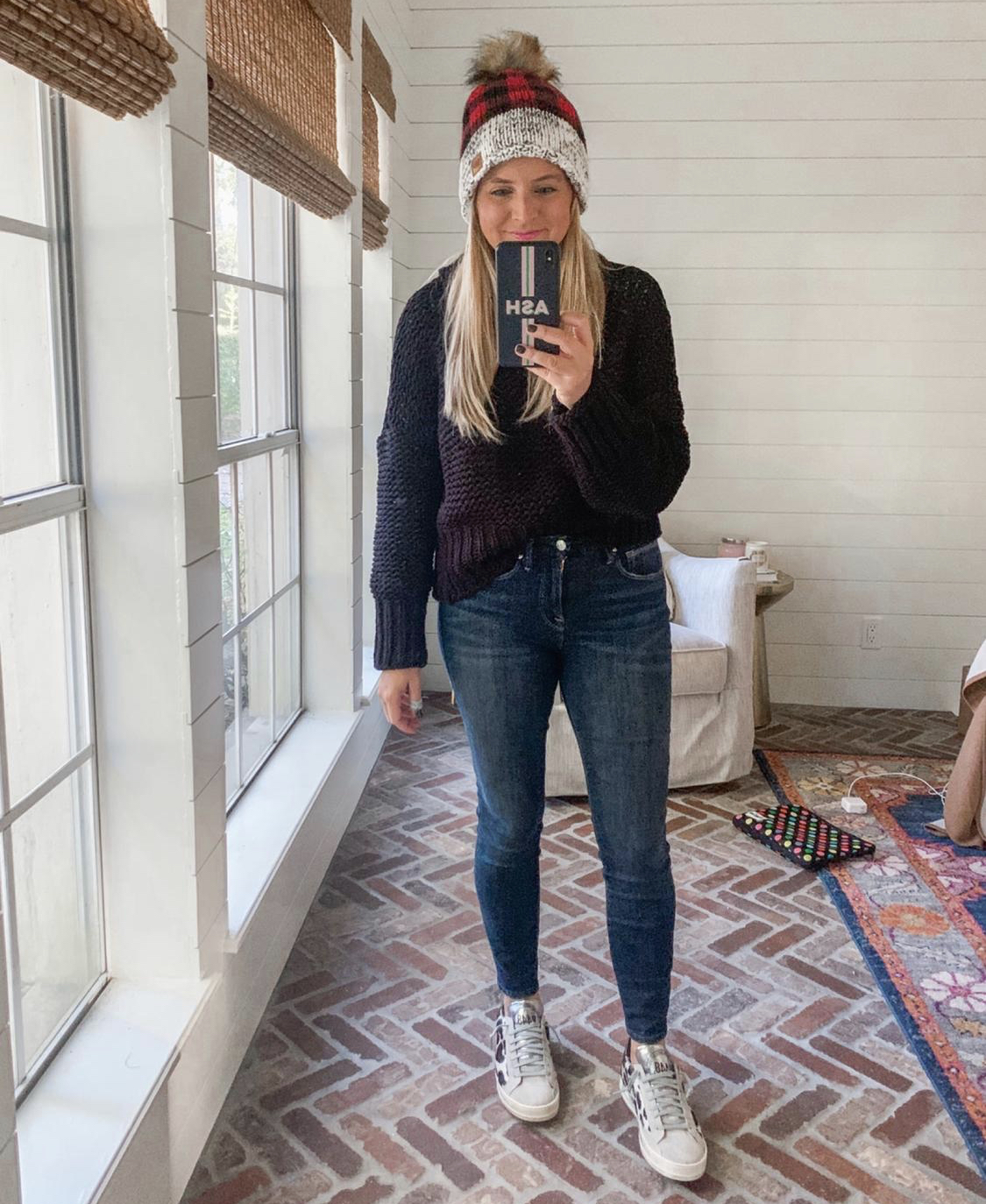 December Outfits by popular Houston fashion blog, Fancy Ashley: image of a woman a black and red buffalo plaid beanie, black cable knit sweater, jeans, and leopard print golden goose sneakers.
