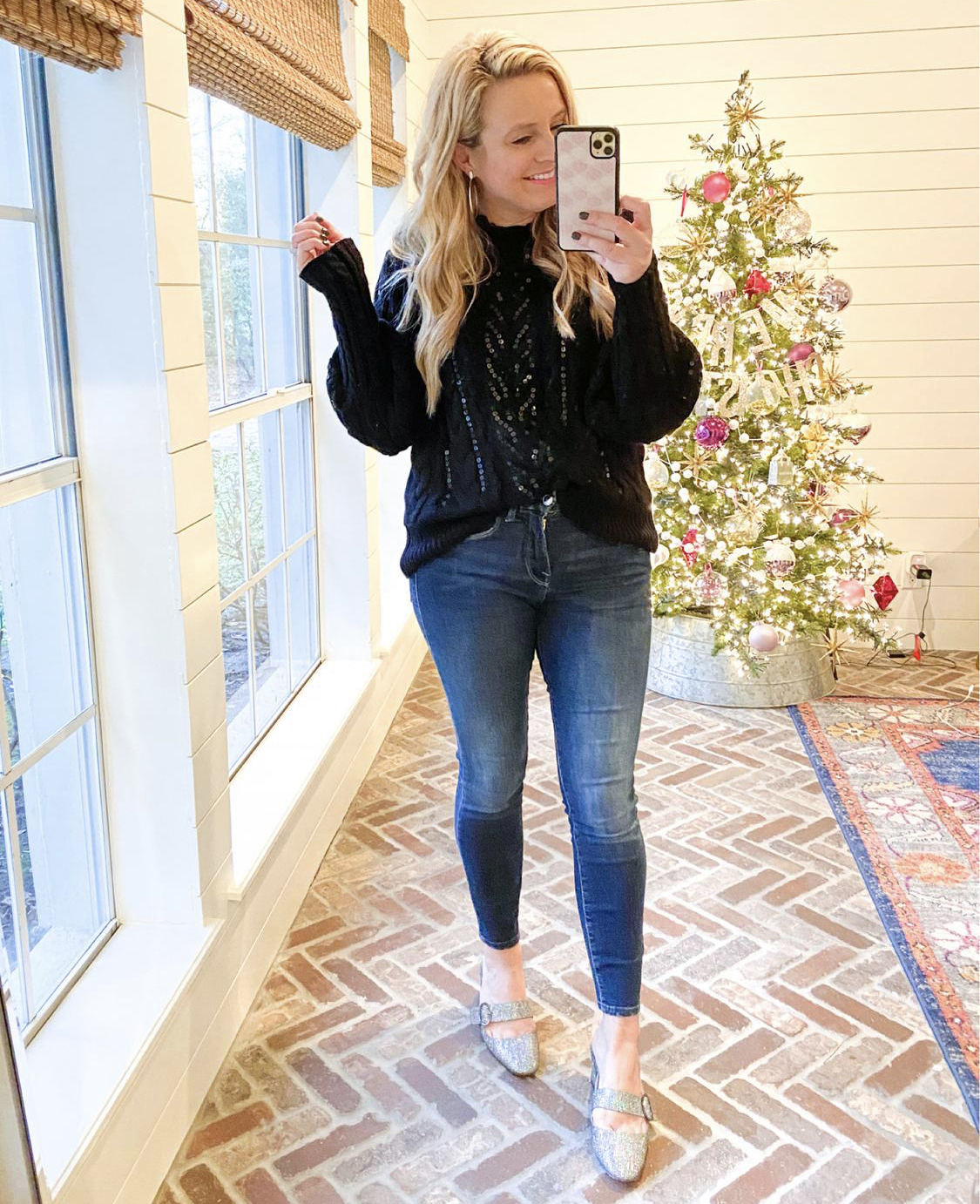 December Outfits by popular Houston fashion blog, Fancy Ashley: image of a woman standing in front of a Christmas tree decorated with pink, white and silver ornaments and wearing a black sequin sweater, jeans, and Sarah Jessica Parker sliver slide heel shoes.