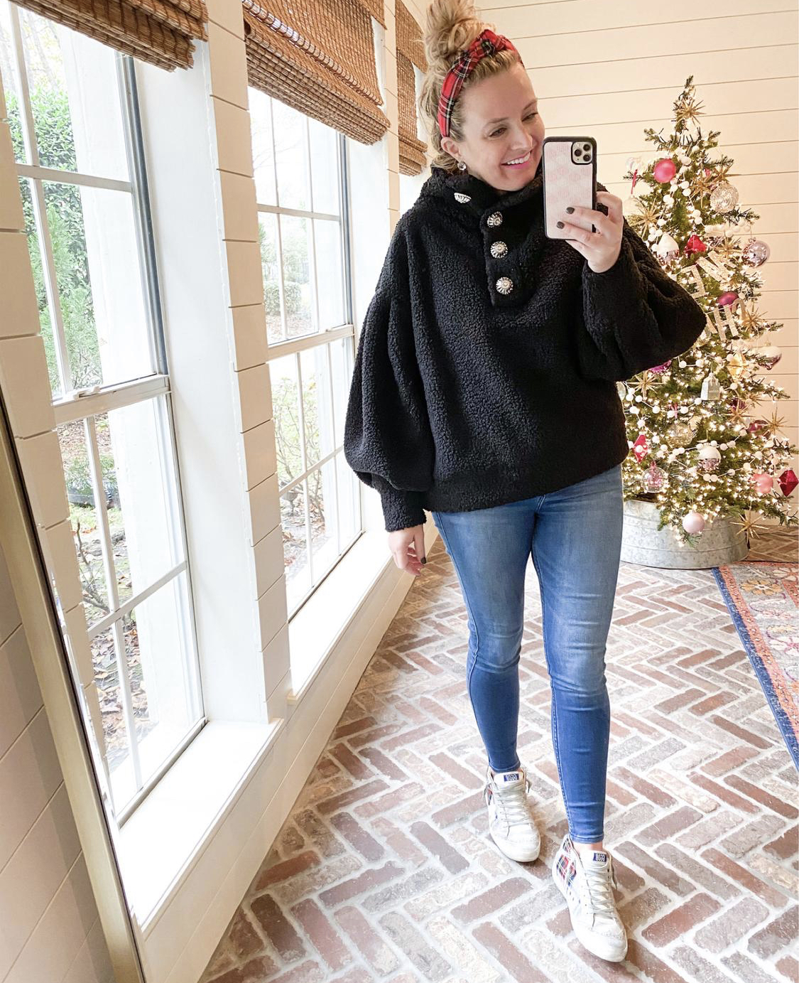 December Outfits by popular Houston fashion blog, Fancy Ashley: image of a woman standing in front of a Christmas tree decorated with pink, white and silver ornaments and wearing a black sherpa bubble sleeve top, jeans, and Golden Goose Sneakers.