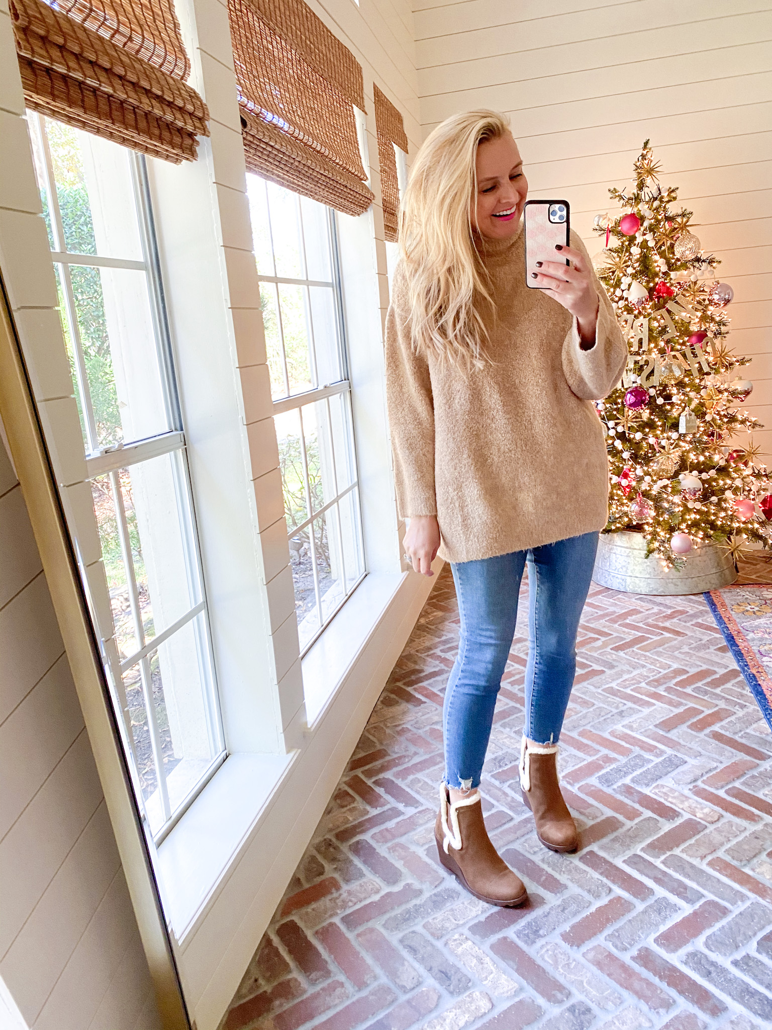December Outfits by popular Houston fashion blog, Fancy Ashley: image of a woman standing in front of a Christmas tree decorated with pink, white and silver ornaments and wearing a tan turtleneck sweater, jeans, and fur lined brown suede boots.