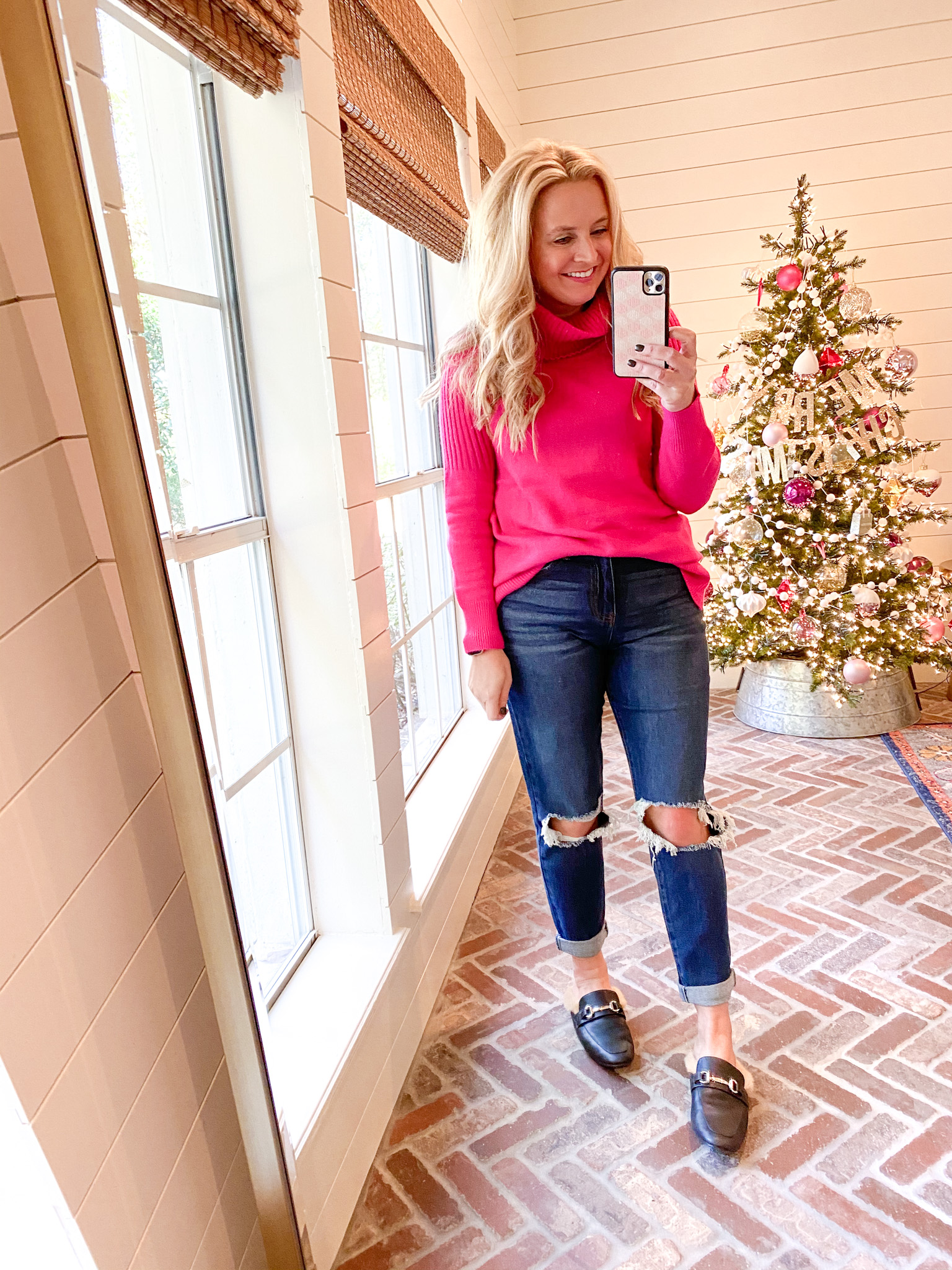 December Outfits by popular Houston fashion blog, Fancy Ashley: image of a woman standing in front of a Christmas tree decorated with pink ornaments and wearing a pink turtleneck sweater, distressed denim and black faux fur lined slide mules.