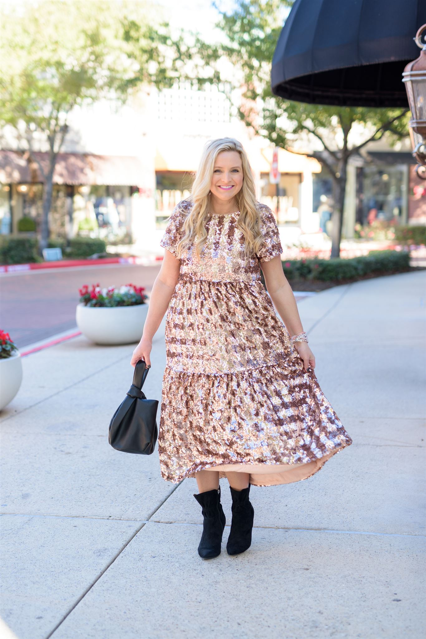 December Outfits by popular Houston fashion blog, Fancy Ashley: image of a woman standing outside on a sidewalk and wearing a gold, silver and copper sequin tiered dress with black suede ankle boots while holding a black purse.