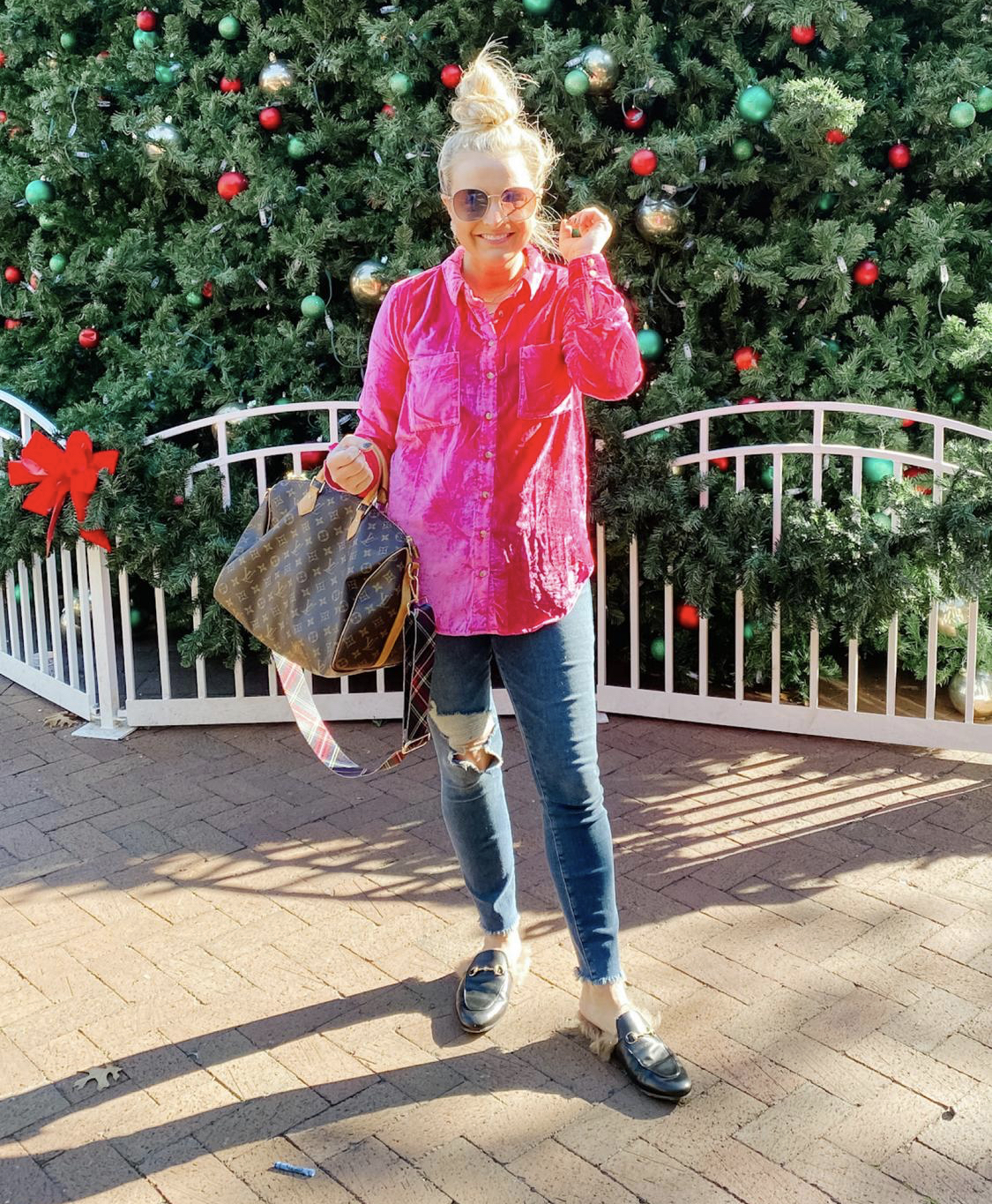 December Outfits by popular Houston fashion blog, Fancy Ashley: image of a woman standing in front of a large Christmas tree and wearing a pink velvet shirt, distressed denim, black faux fur lined slide mules, and holding a Louis Vuitton bag.