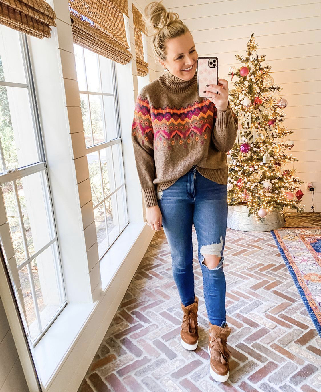 December Outfits by popular Houston fashion blog, Fancy Ashley: image of a woman standing in front of a Christmas tree decorated with pink, white and silver ornaments and wearing a brown, pink and orange nordic print turtleneck sweater, distressed denim, and brown fur lined hightop sneakers.