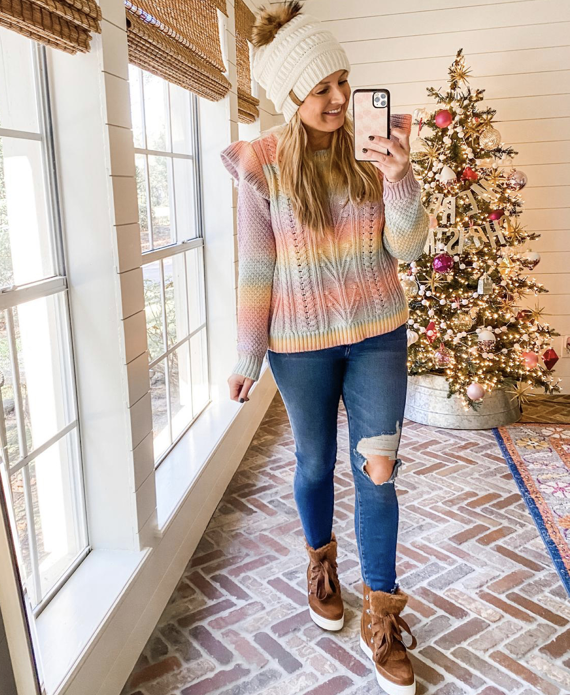 December Outfits by popular Houston fashion blog, Fancy Ashley: image of a woman standing in front of a Christmas tree decorated with pink, white and silver ornaments and wearing a multi color stripe knit sweater, cream fur pom beanie, distress denim, and brown fur lined hight tops sneakers.