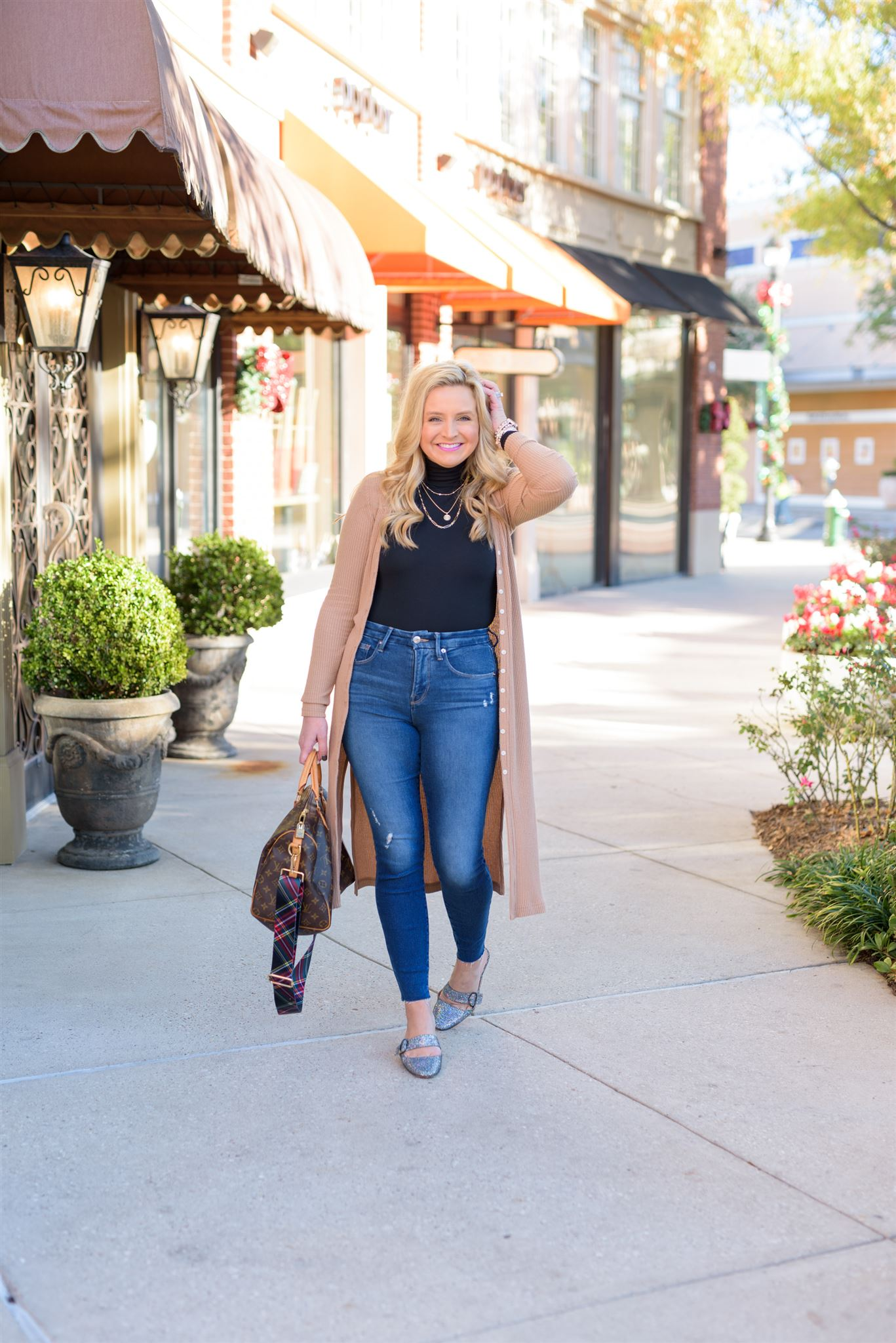 December Outfits by popular Houston fashion blog, Fancy Ashley: image of a woman standing outside and wearing a black turtleneck shirt, tan long line cardigan, jeans, and sliver slide flats while holding a Louis Vuitton bag.