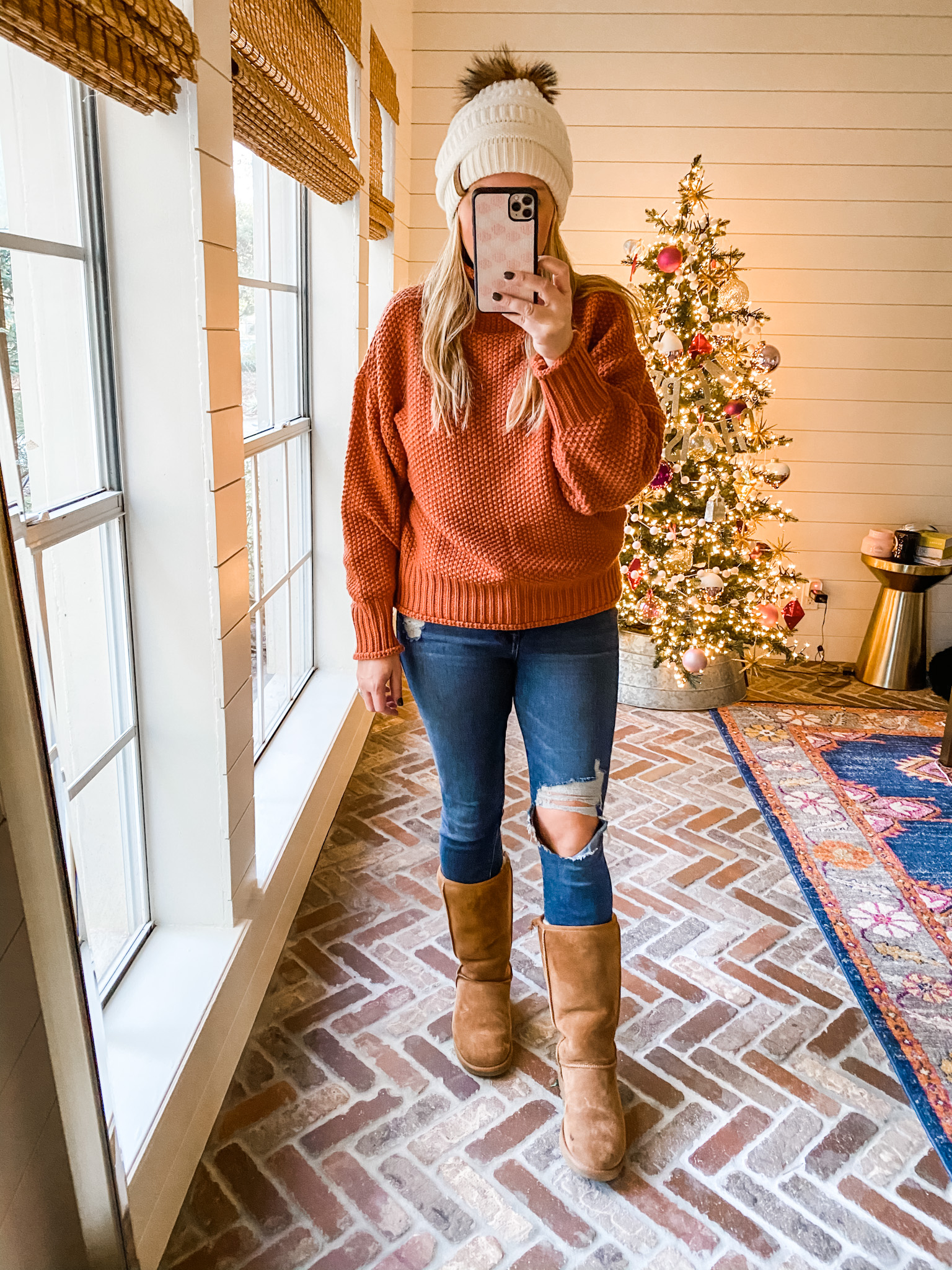 December Outfits by popular Houston fashion blog, Fancy Ashley: image of a woman standing in front of a Christmas tree decorated with pink, white and silver ornaments and wearing a orange cable knit sweater, distressed denim, cream fur pom beanie, and brown suede Ugg boots.