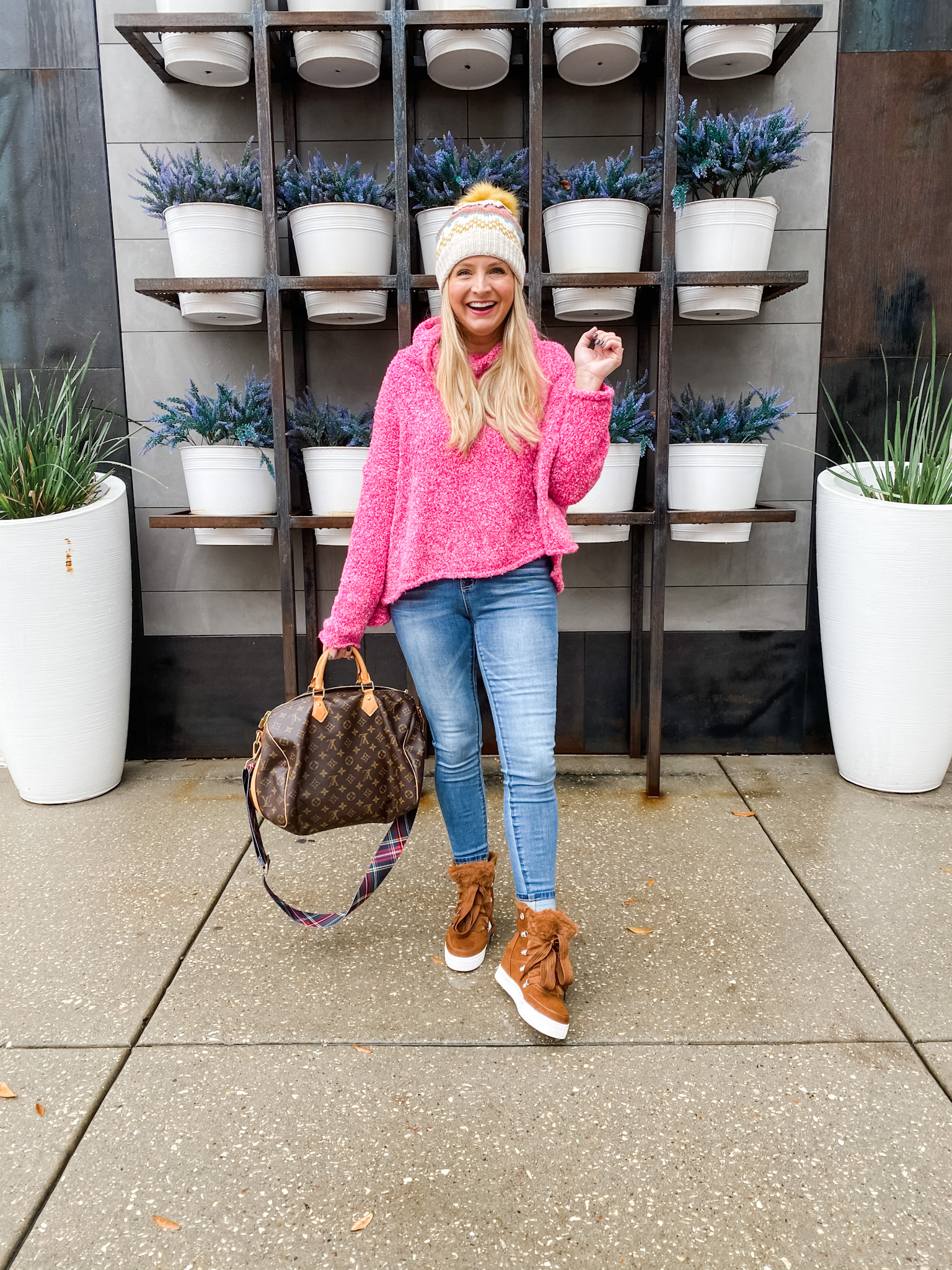 December Outfits by popular Houston fashion blog, Fancy Ashley: image of a woman standing outside and wearing pink hooded pullover sweater, jeans, brown suede fur lined high top sneakers, and cream fur pom beanie while holding a Louis Vuitton bag.