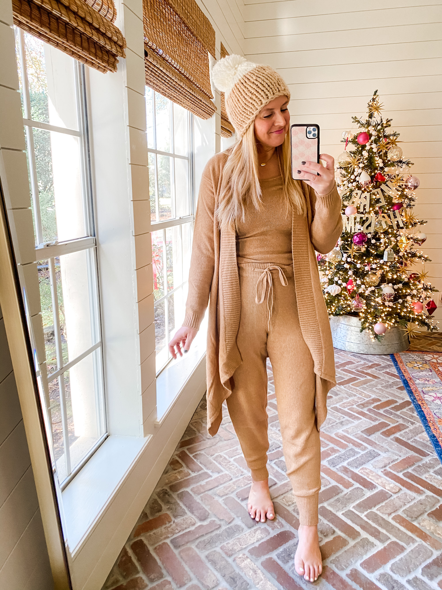 December Outfits by popular Houston fashion blog, Fancy Ashley: image of a woman standing in front of a Christmas tree decorated with pink, white and silver ornaments and wearing a tan sweater set, tan sweater and tan and cream pom beanie.