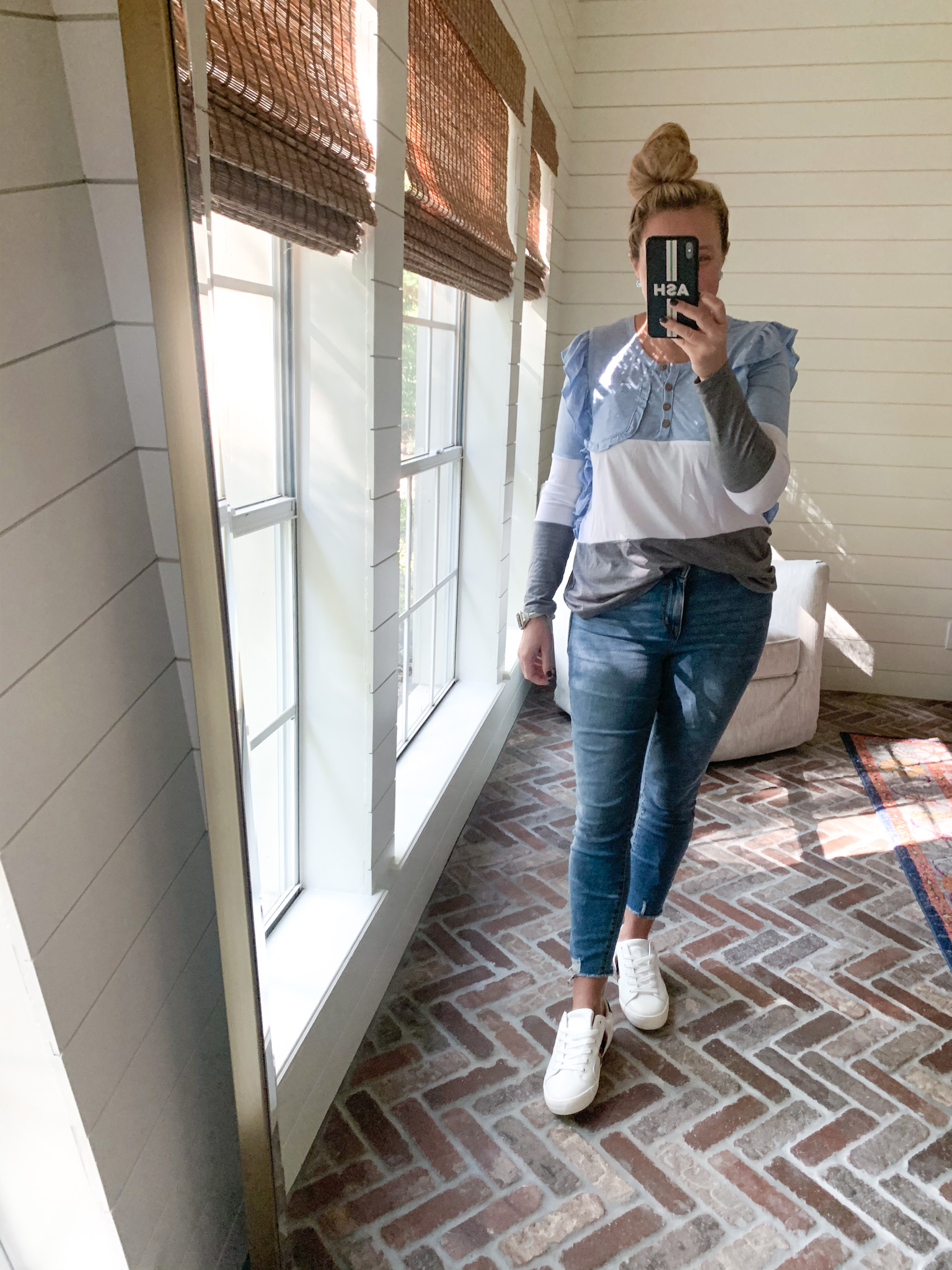 Cute Fall Outfits by popular Houston fashion blog, Fancy Ashley: image of a woman wearing a blue, white and grey stripe long sleeve top with jeans and a pair of white sneakers.
