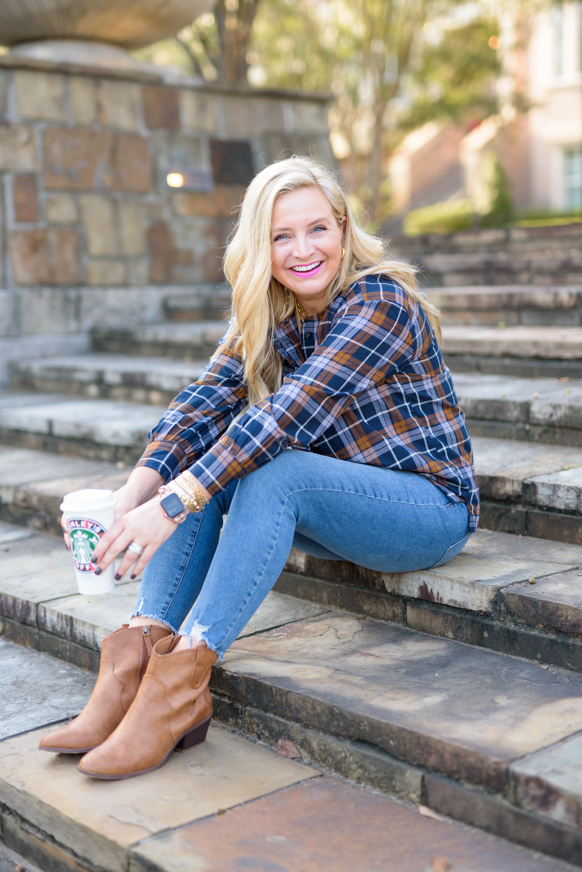 Fall Plaid by popular Houston fashion blog, Fancy Ashley: image of a woman wearing a a blue and brown plaid top, distressed hem jeans, and brown ankle boots.