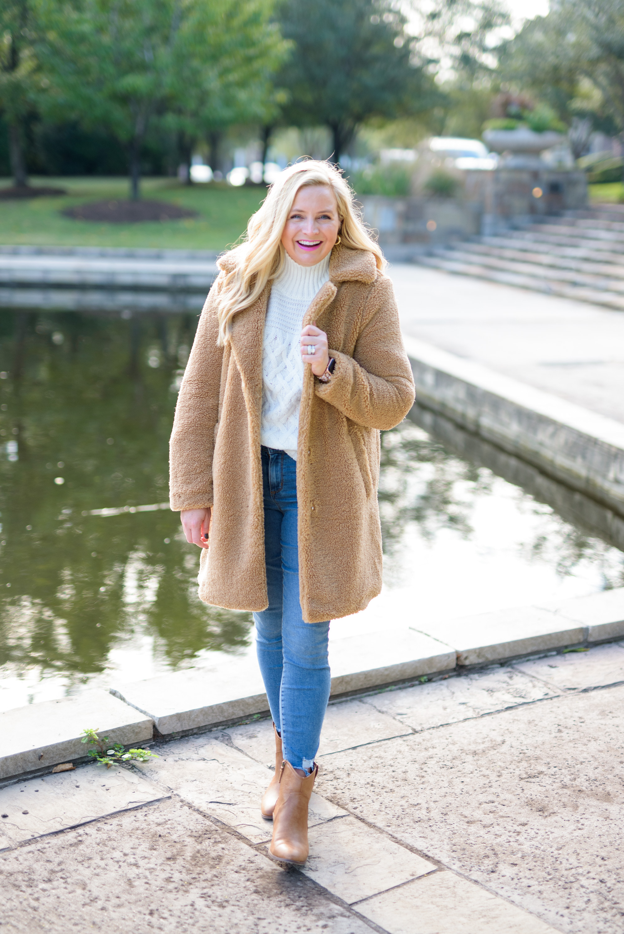 Cute Fall Outfits by popular Houston fashion blog, Fancy Ashley: image of a woman wearing a wubby fleece jacket, cream sweater, jeans, tan ankle boots and gold hoop earrings.
