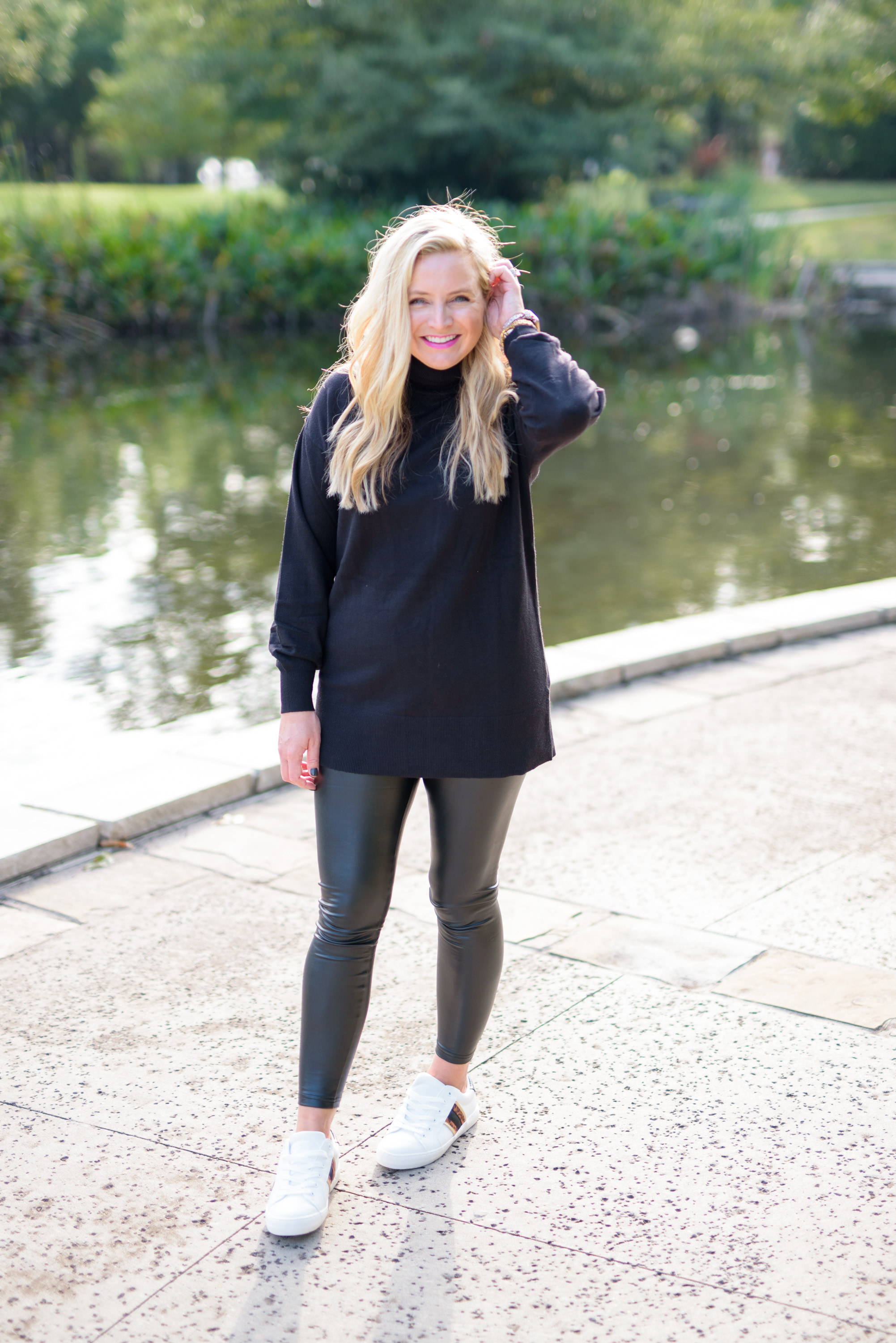 Faux Leather by popular Houston fashion blog, Fancy Ashley: image of a woman wearing a pair of faux leather leggings, white sneakers, and a black turtleneck sweater.
