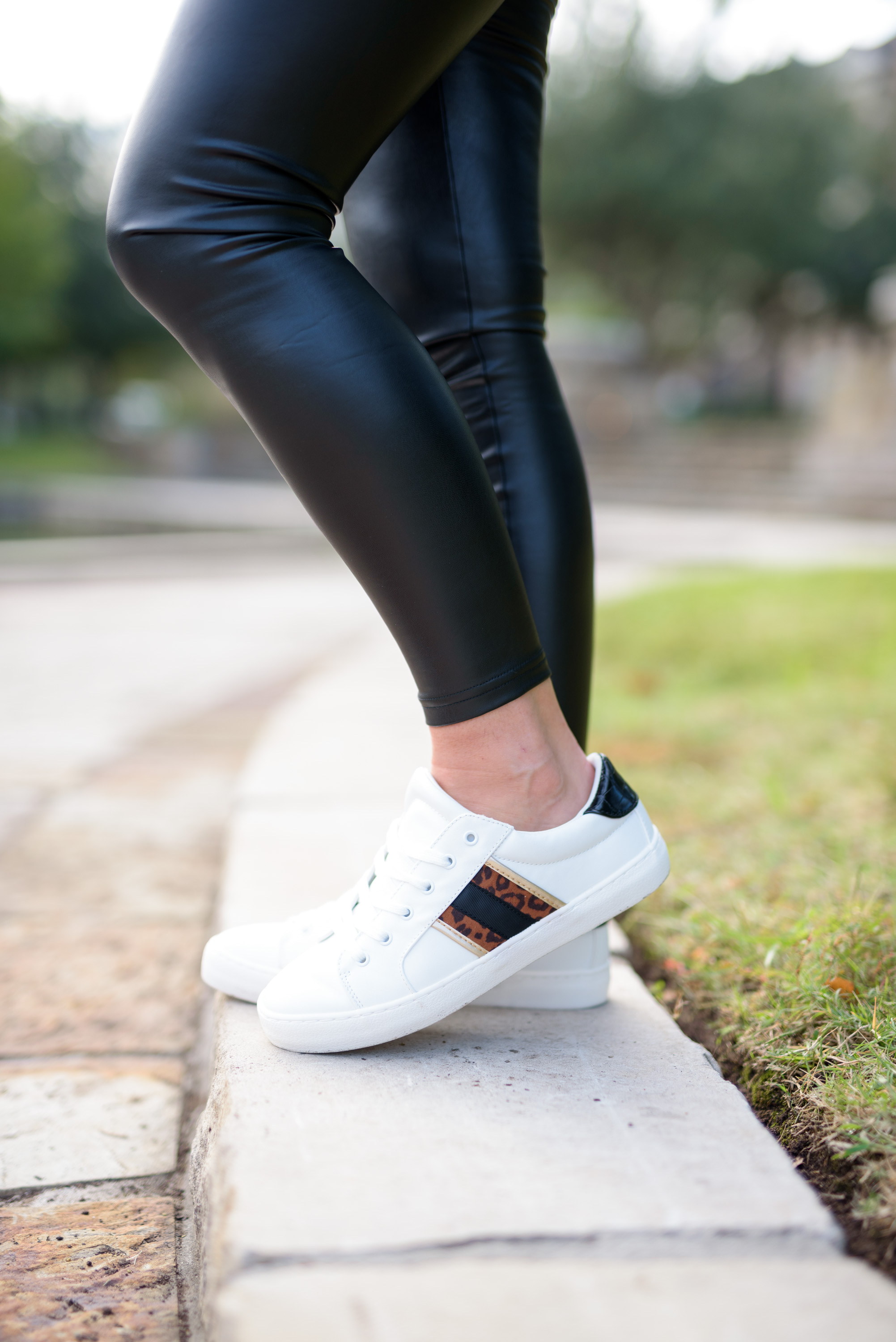 Faux Leather by popular Houston fashion blog, Fancy Ashley: image of a woman wearing a pair of faux leather leggings and white sneakers.
