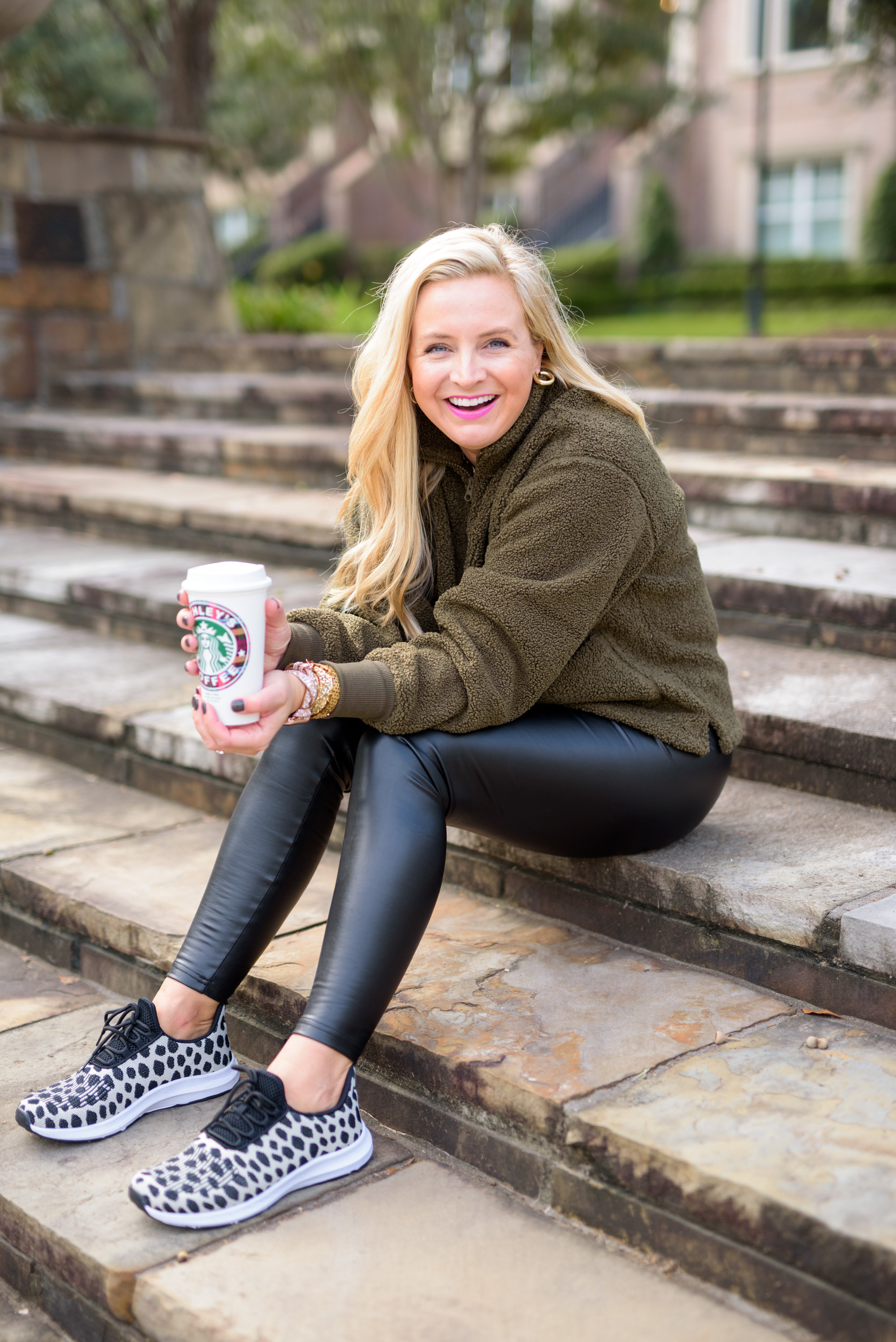 Cute Fall Outfits by popular Houston fashion blog, Fancy Ashley: image of a woman wearing a wubby fleece pullover, faux leather leggings, sneakers, gold hoop earrings, and holding a Starbuck's hot cup.