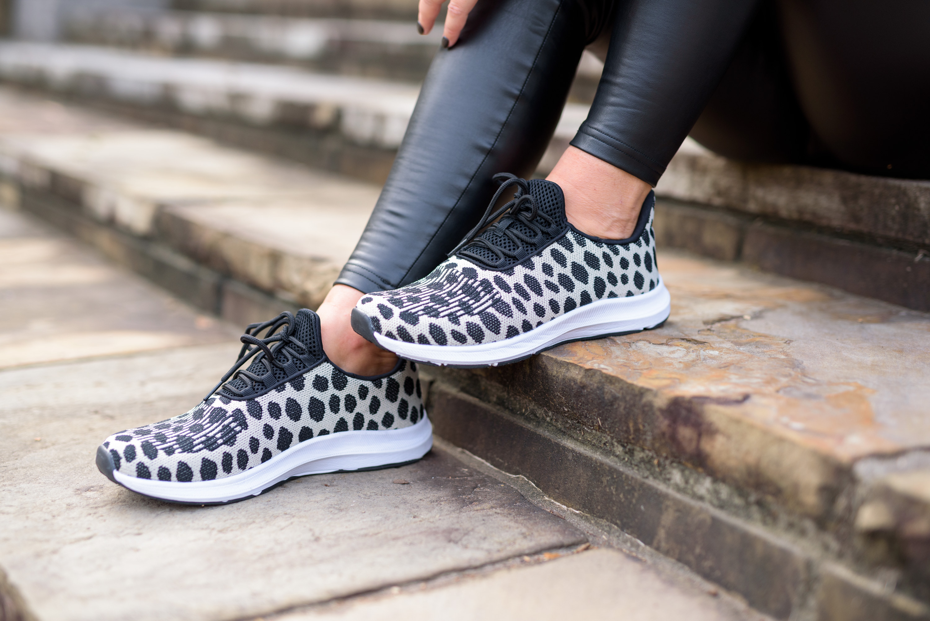 Faux Leather by popular Houston fashion blog, Fancy Ashley: image of a woman wearing a pair of faux leather leggings and athletic sneakers.