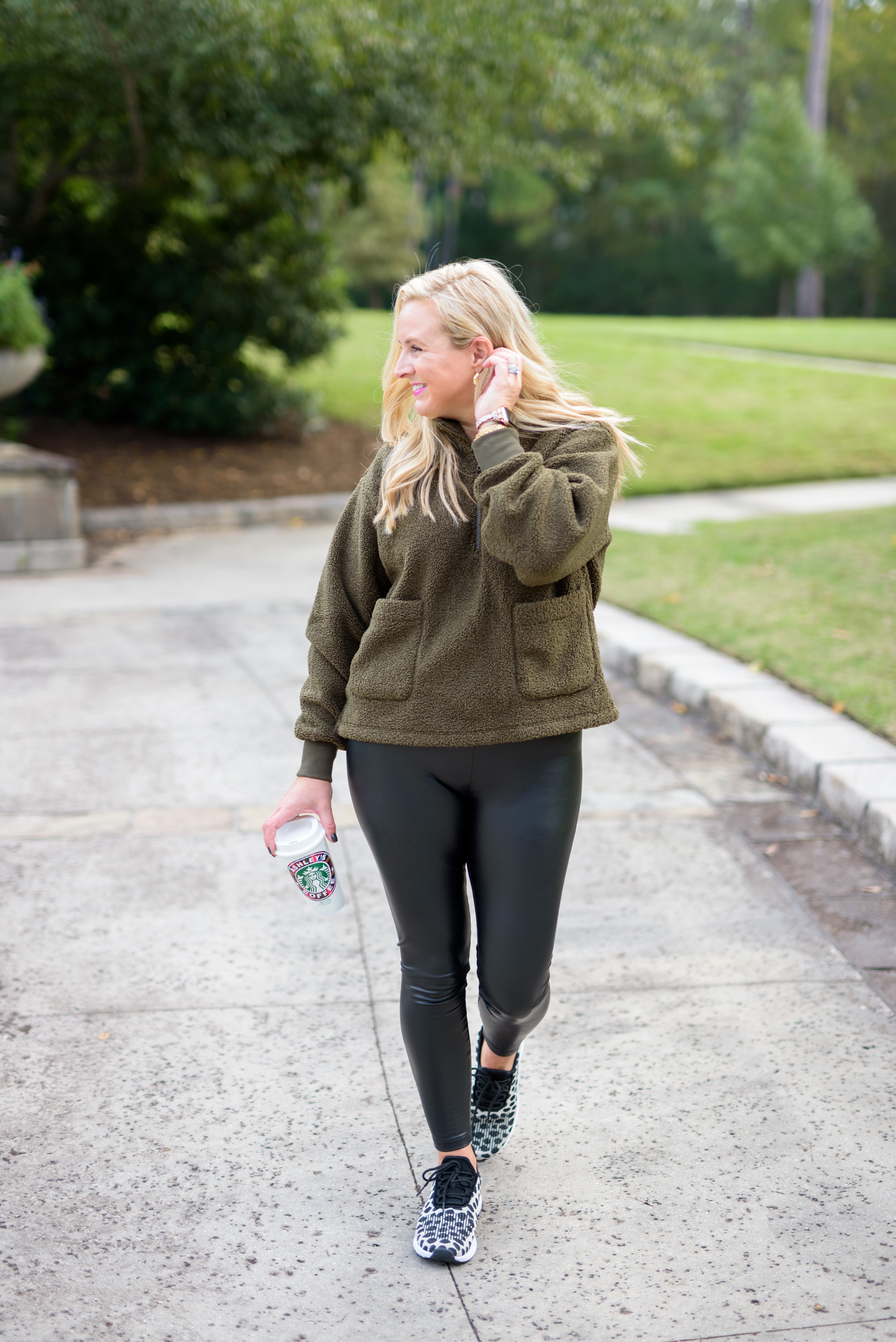 Faux Leather by popular Houston fashion blog, Fancy Ashley: image of a woman wearing a pair of faux leather leggings, sneakers, and a green fleece pull over.