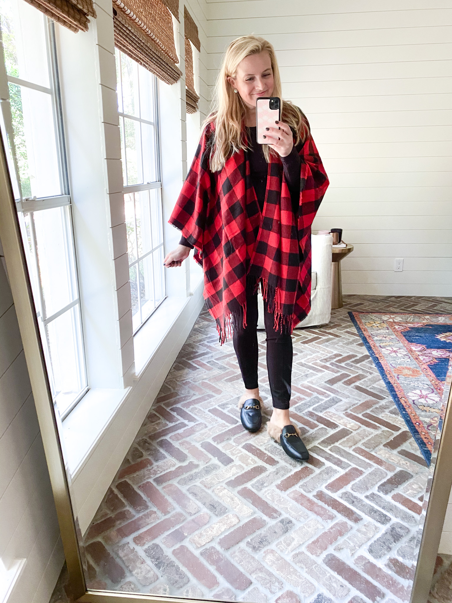 Prime Day by popular Houston fashion blog, Fancy Ashley: image of a woman wearing a Amazon black and red buffalo plaid poncho, black leggings, and black mules.