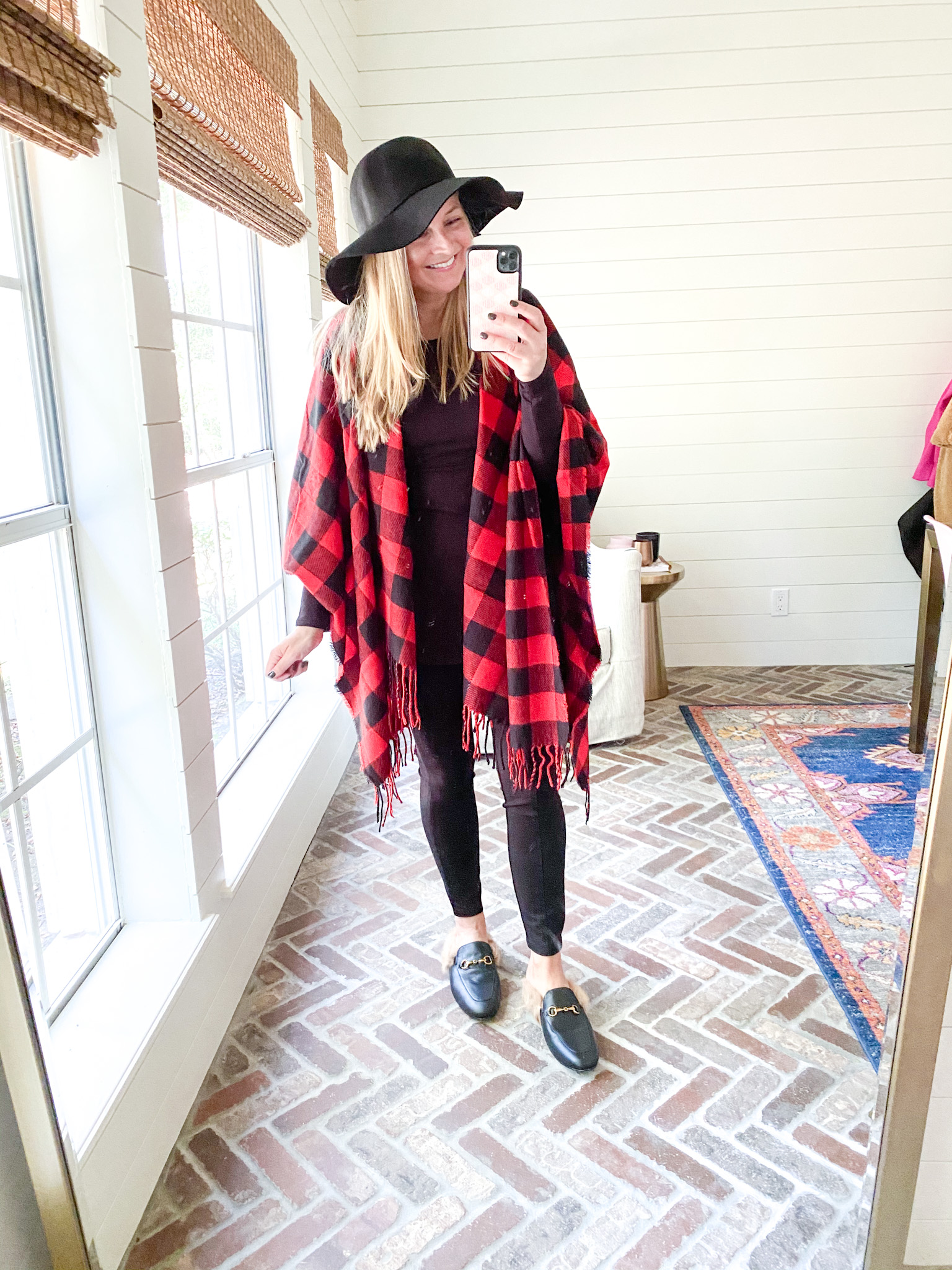 Prime Day by popular Houston fashion blog, Fancy Ashley: image of a woman wearing a Amazon black and red buffalo plaid poncho, felt floppy hat, black leggings, and black mules.