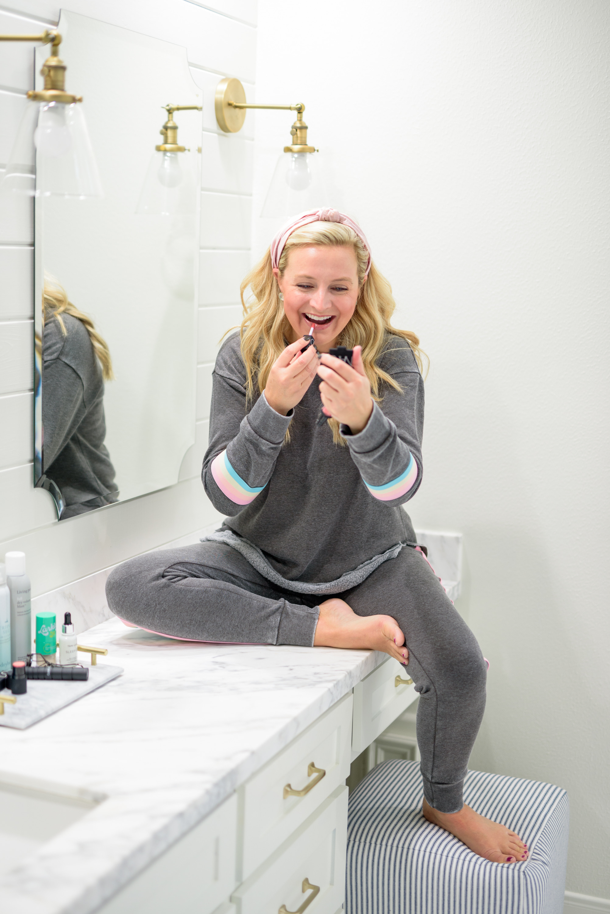 Fall Beauty by popular Houston beauty blog, Fancy Ashley: image of a woman sitting on her bathroom vanity and wearing a Burnout Stripe Sweatshirt VINTAGE HAVANA and Burnout Stripe Joggers VINTAGE HAVANA and applying lipgloss.