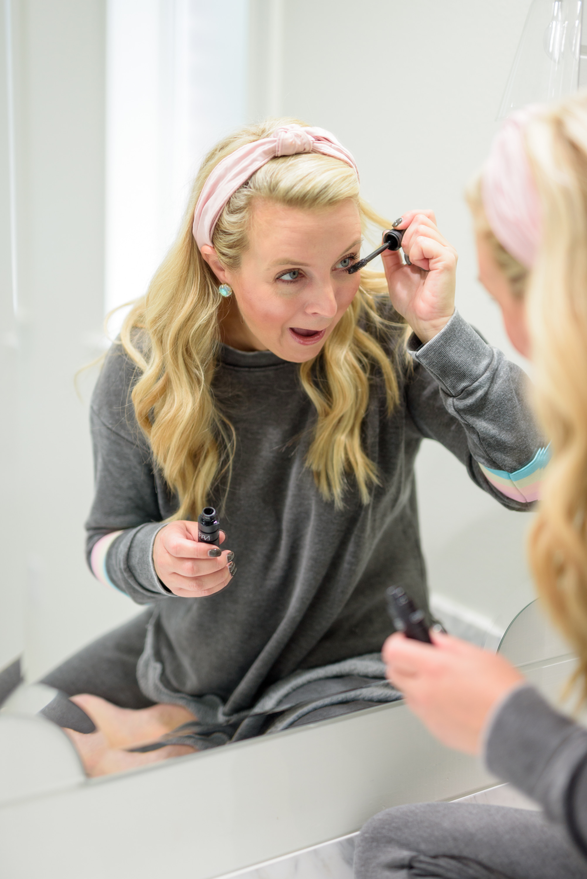 Fall Beauty by popular Houston beauty blog, Fancy Ashley: image of a woman sitting on her bathroom vanity and wearing a Burnout Stripe Sweatshirt VINTAGE HAVANA and Burnout Stripe Joggers VINTAGE HAVANA and applying mascara.