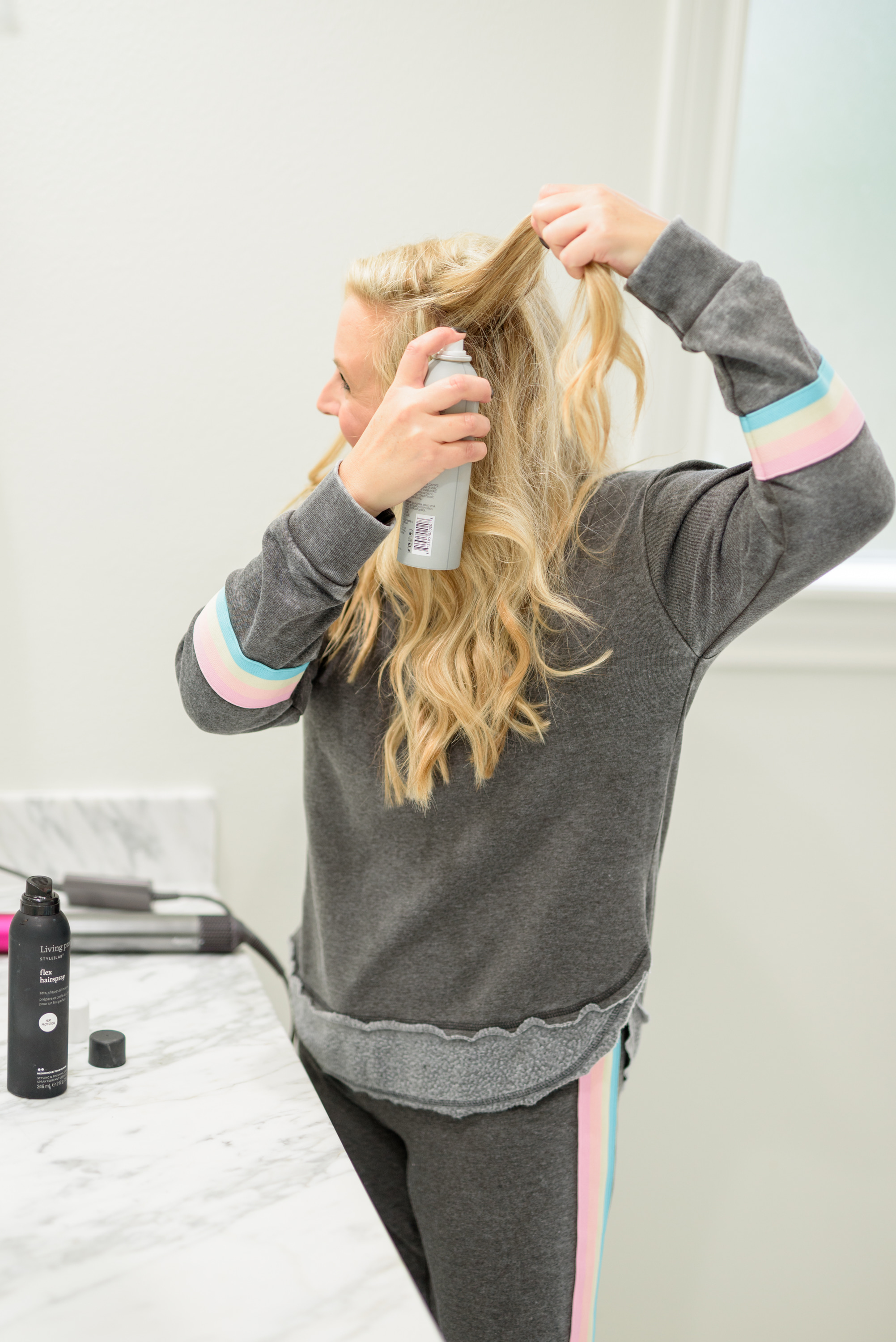 Fall Beauty by popular Houston beauty blog, Fancy Ashley: image of a woman sitting on her bathroom vanity and wearing a Burnout Stripe Sweatshirt VINTAGE HAVANA and Burnout Stripe Joggers VINTAGE HAVANA and using Living Proof dry shampoo.