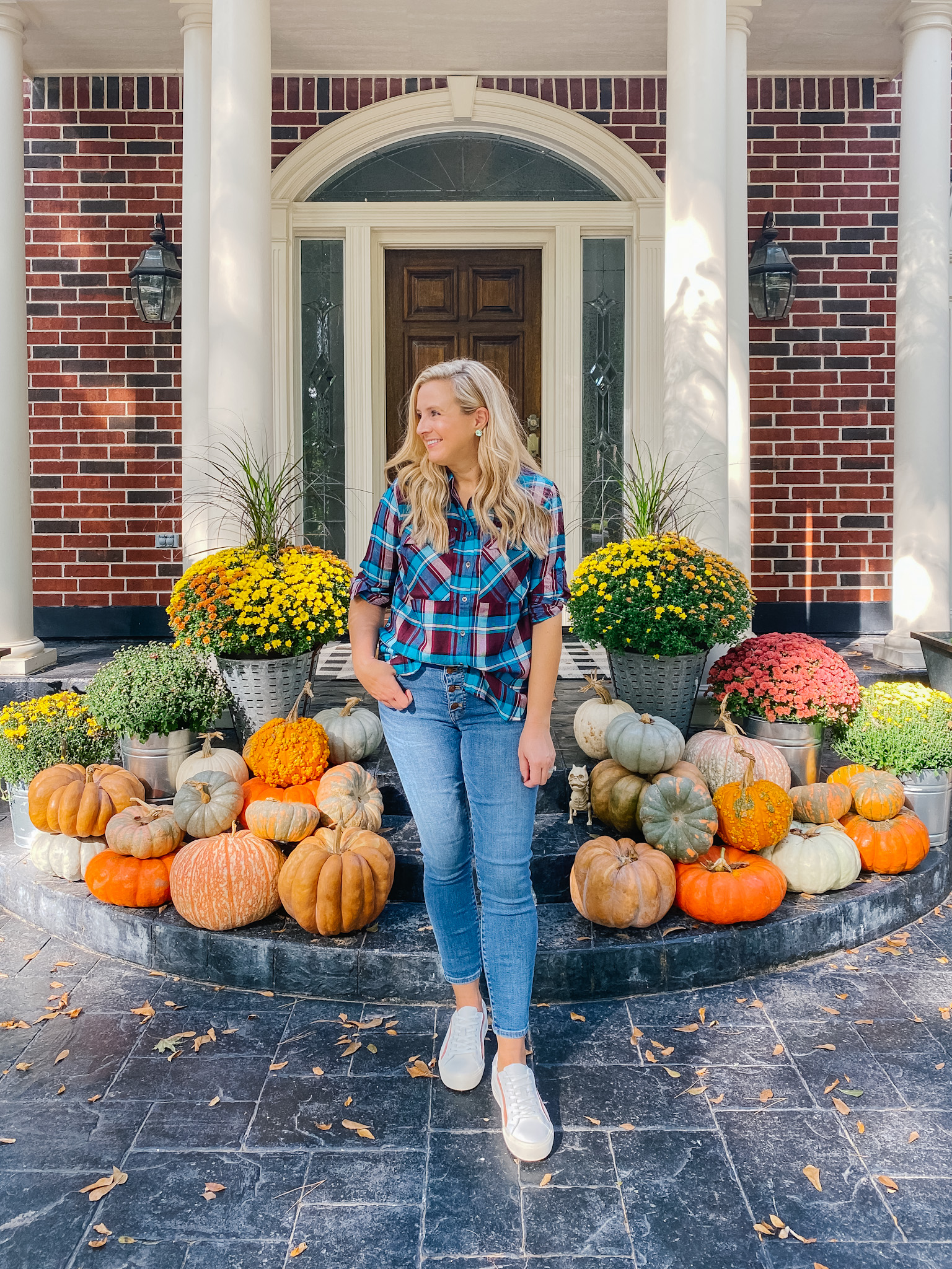 Fall Plaid by popular Houston fashion blog, Fancy Ashley: image of a woman standing in front of a front porch decorated with pumpkins and potted mums and wearing a plaid top, jeans, and white sneakers.