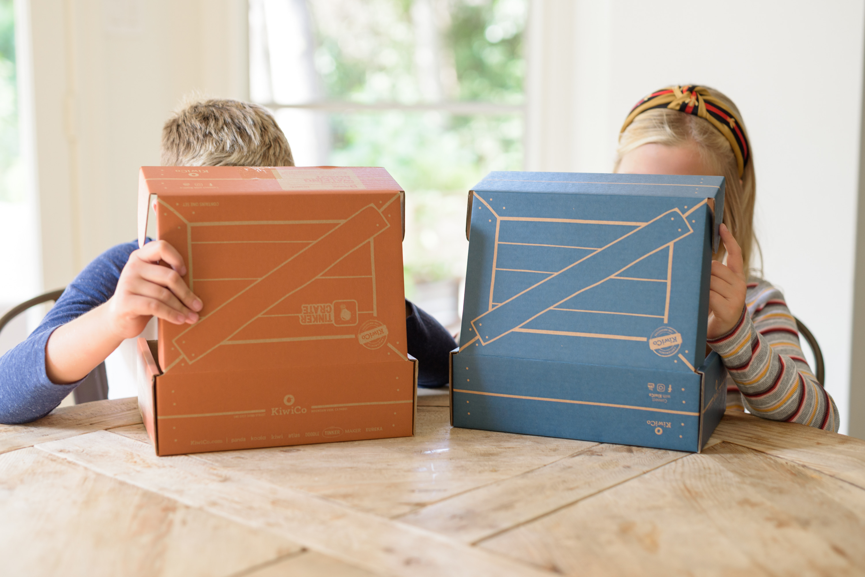 Kiwico Reviews by popular Houston lifestyle blog, Fancy Ashley: image of two kids looking at Kiwico boxes.