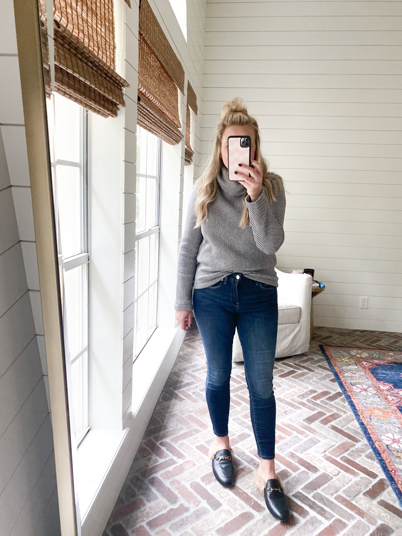 Cute Fall Outfits by popular Houston fashion blog, Fancy Ashley: image of a woman wearing a black and white pullover, jeans, and a faux fur lined slide black mules.