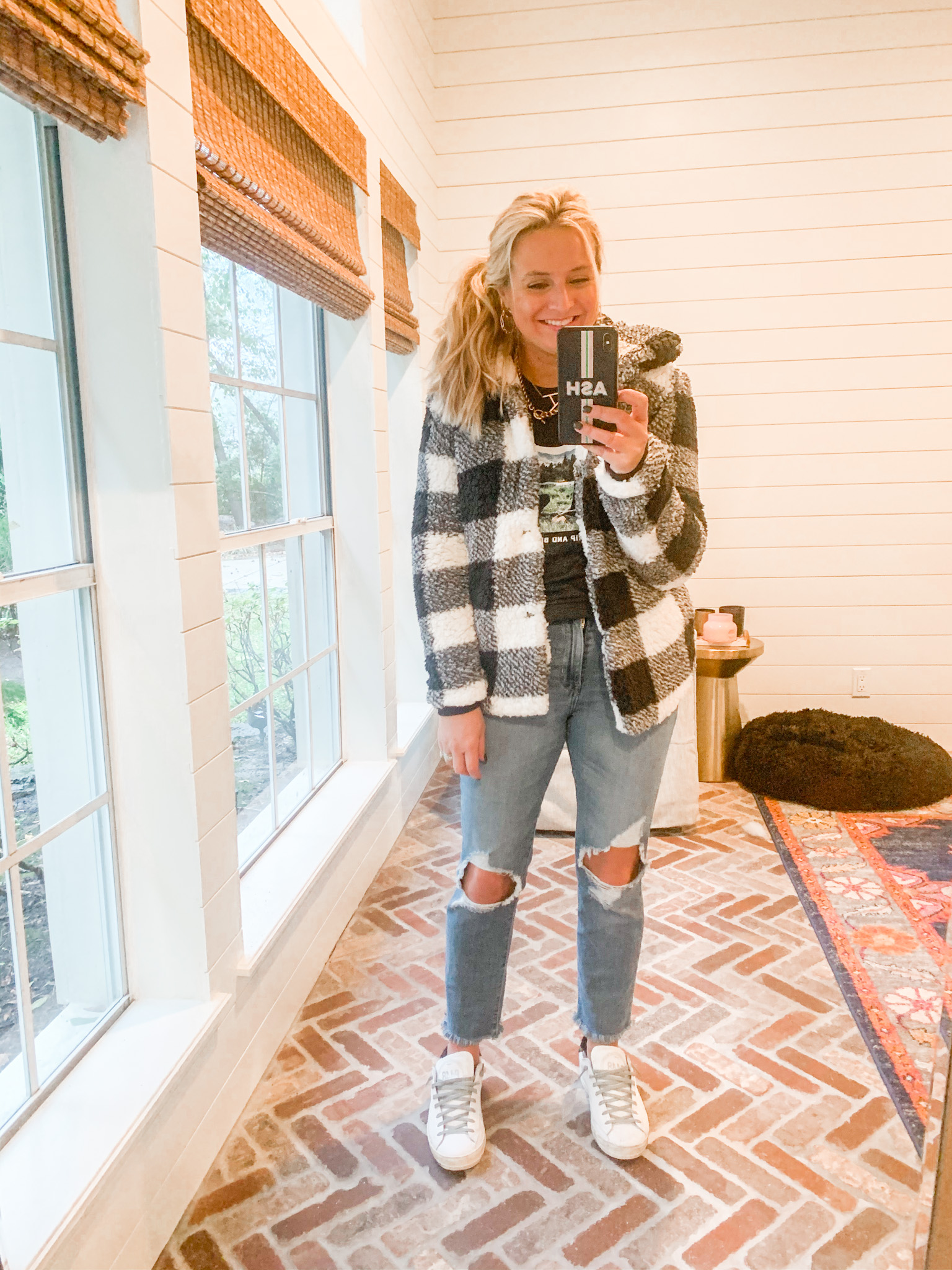 Cute Fall Outfits by popular Houston fashion blog, Fancy Ashley: image of a woman wearing a black and white buffalo plaid jacket, black t-shirt, distressed jeans, gold hoop earrings, and white sneakers.